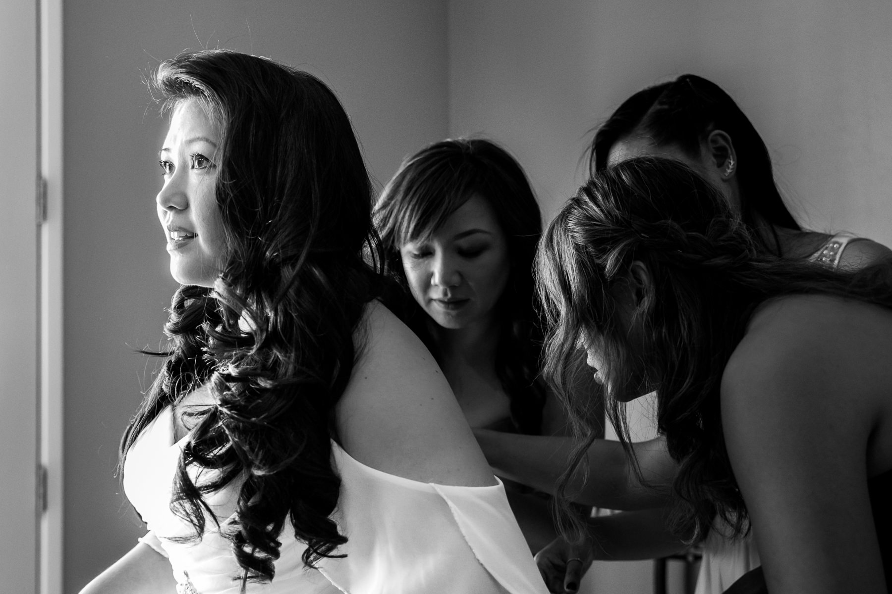 black and white photo of bride putting on wedding dress with bridesmaids at noor wedding photography