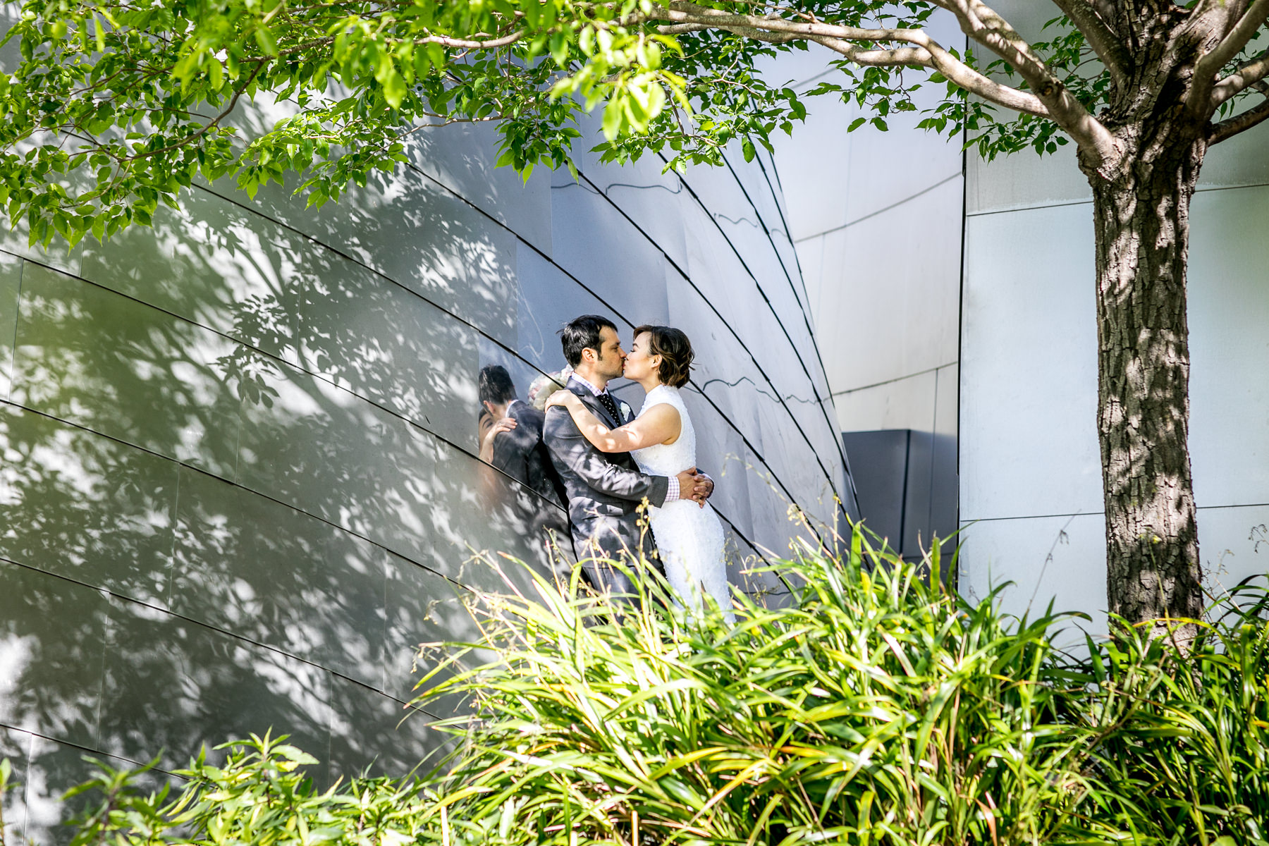bride and groom kiss after wedding at disney concert hall