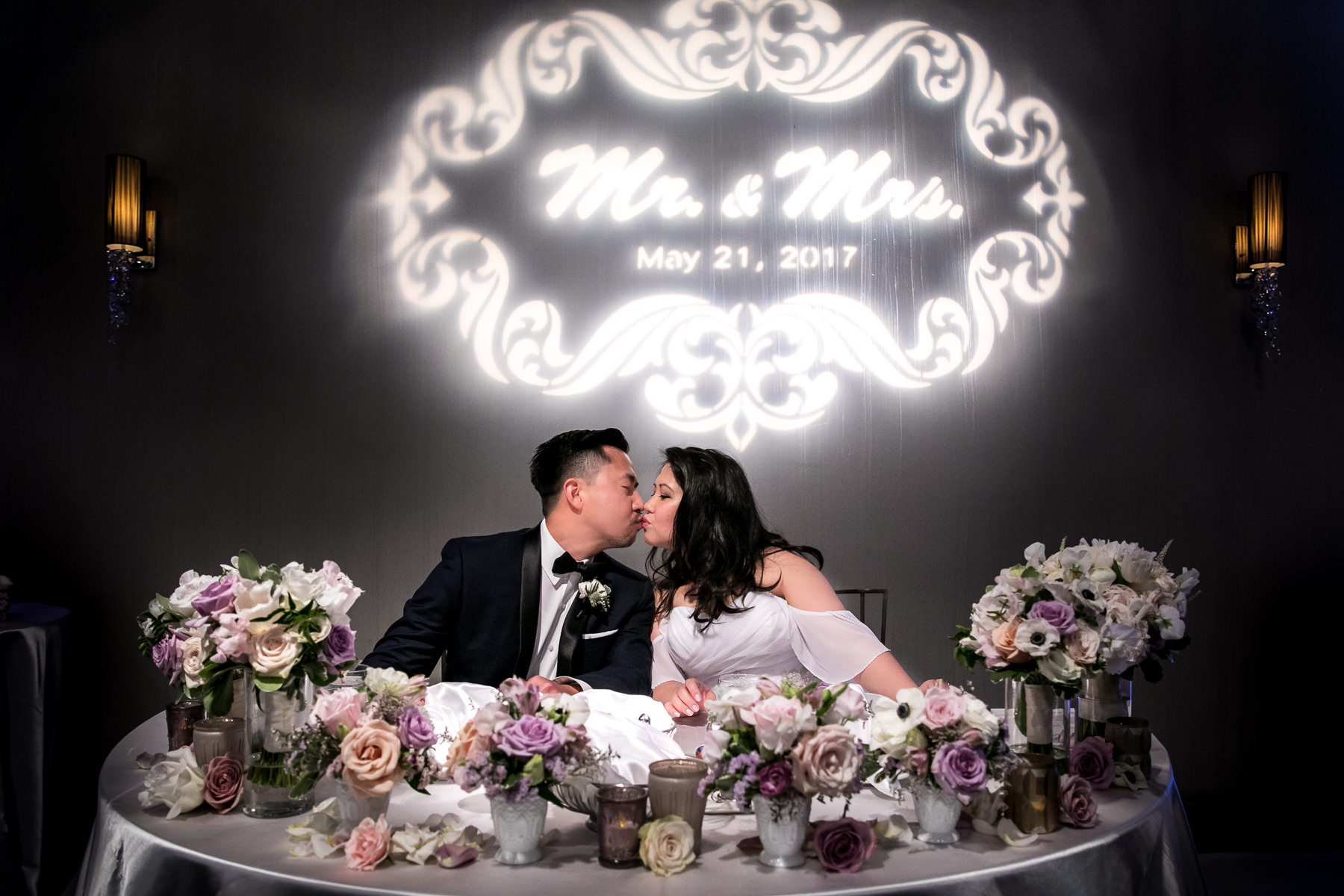 bride and groom kiss at sweetheart table with wen floral arrangements at noor pasadena wedding photographer