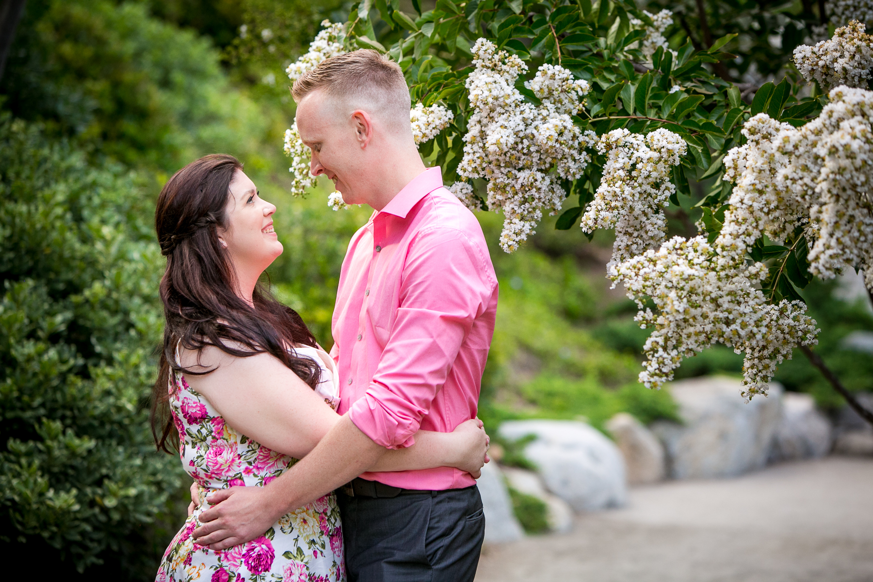 pink floral dress and pink dress shirt pop in garden engagement session photo