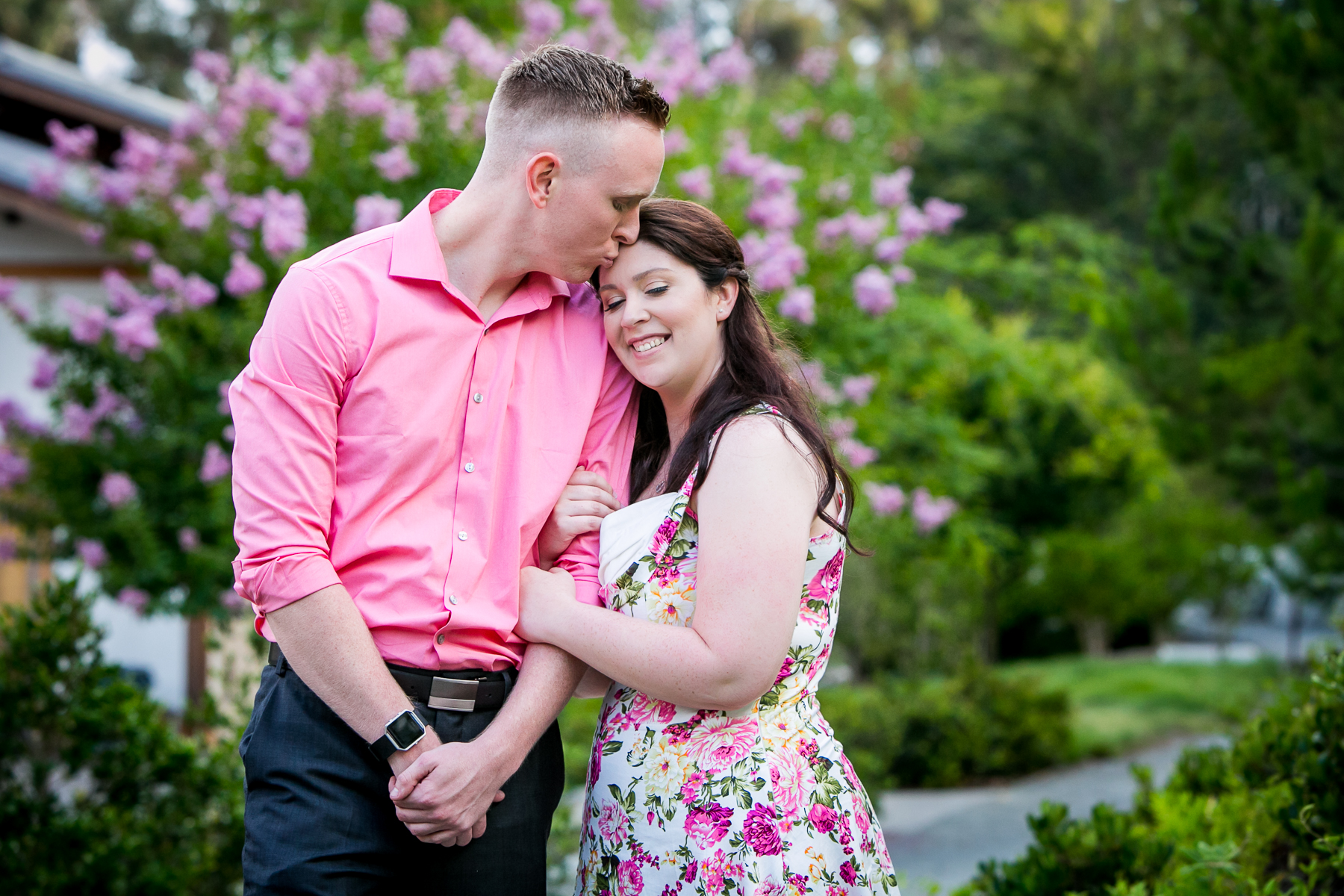 groom-to-be gives bride-to-be kiss on forehead during balboa park engagement session