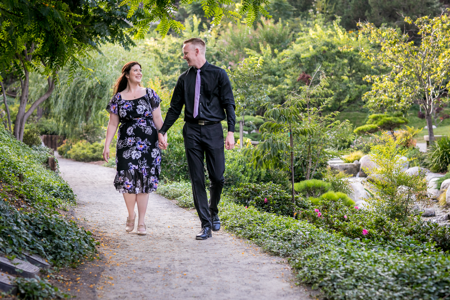 couple changes clothes into black formal attire at japanese friendship garden engagement session