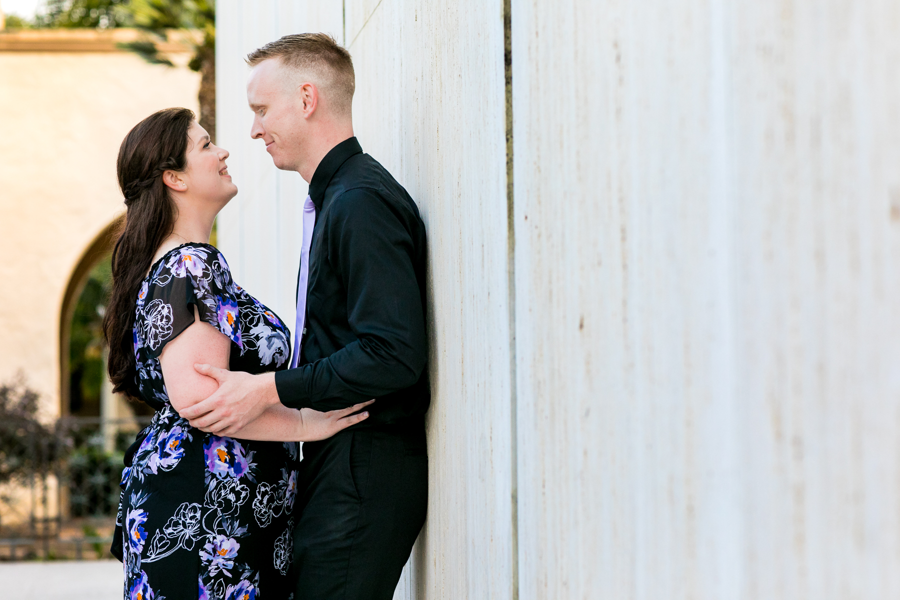 girl in black dress close as guy in black dress shirt leans up against wall during san diego engagement session