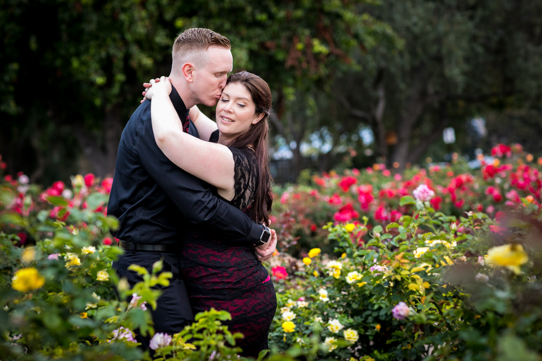 kiss in the middle of the rose garden at balboa park san diego engagement session
