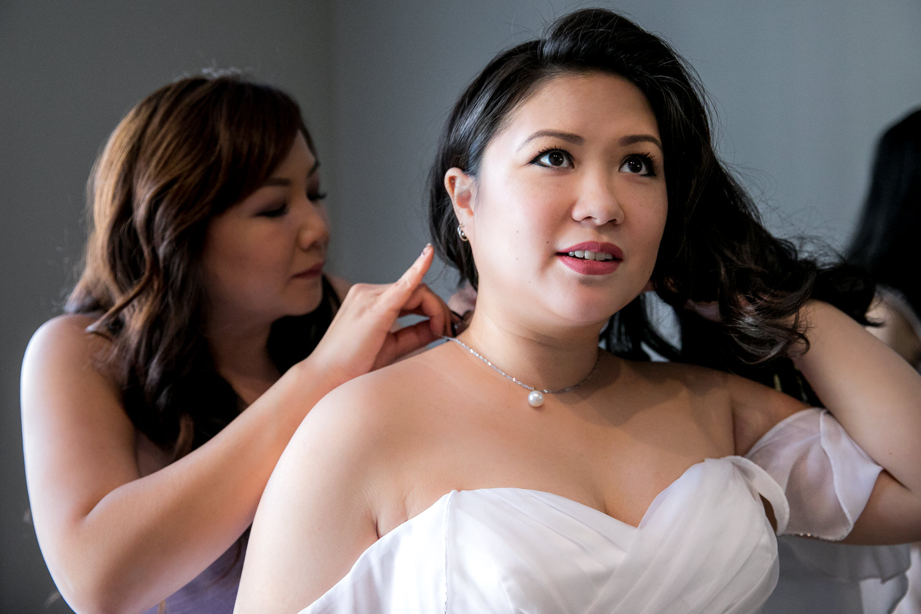 maid of honor puts necklace on bride at noor pasadena wedding getting ready