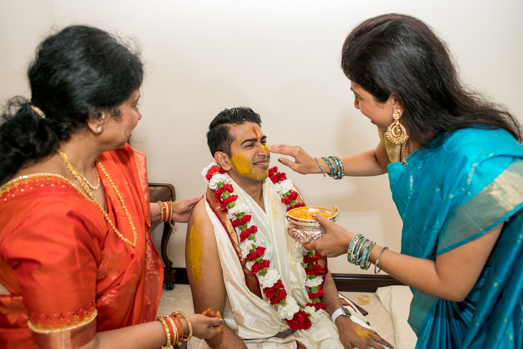 sister applies haldi to hindu groom's nose in whittier wedding photographer