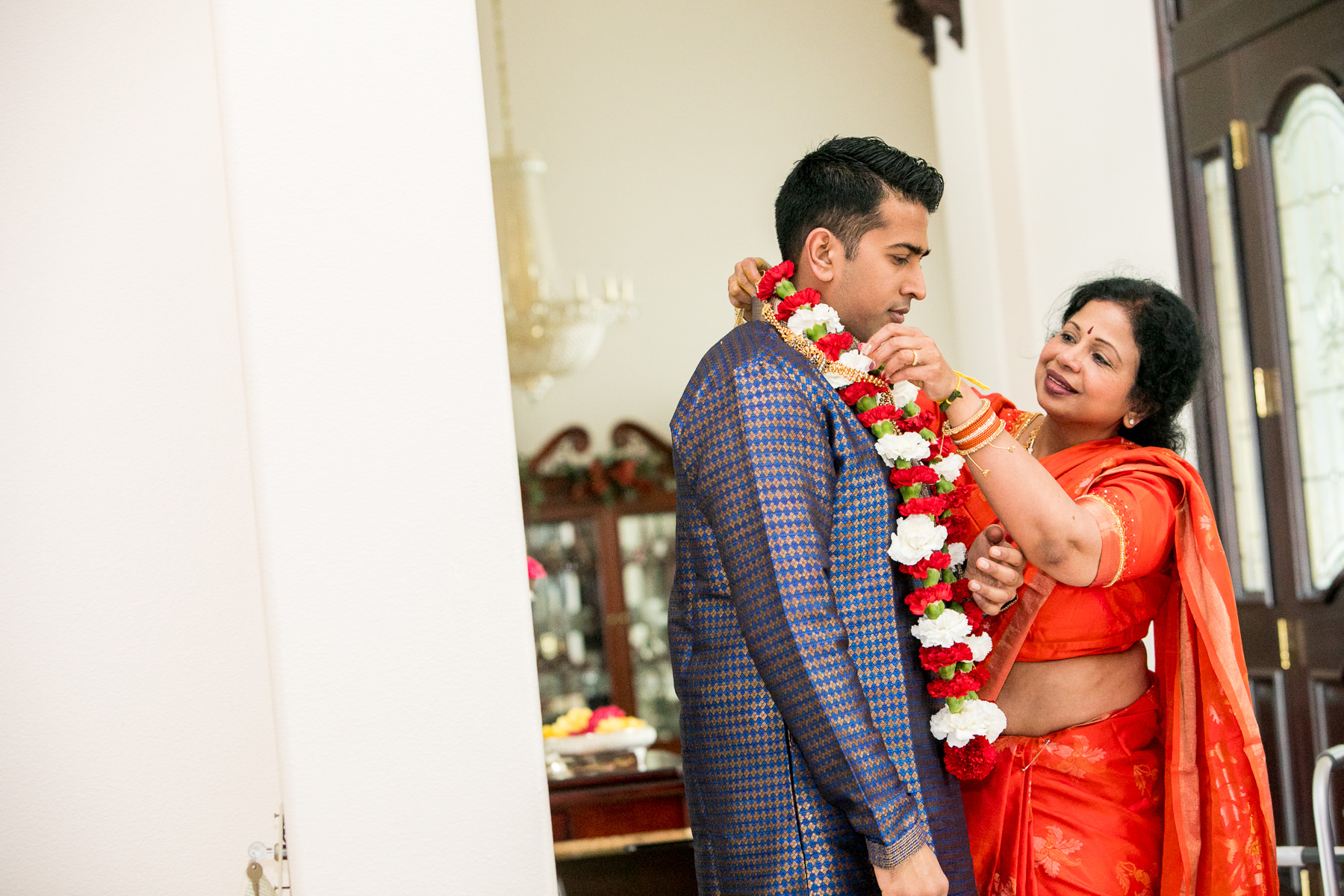 intimate moment with mother and indian groom getting garland in whittier wedding