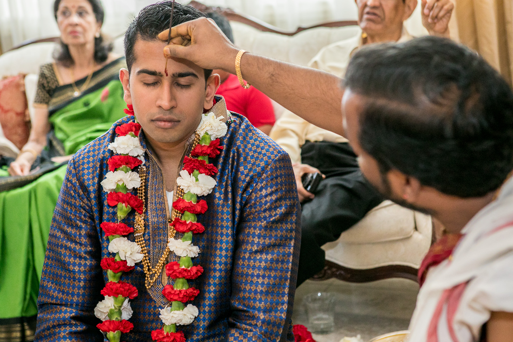 red tilaka applied on indian groom's forehead during pre indian wedding rituals in whittier