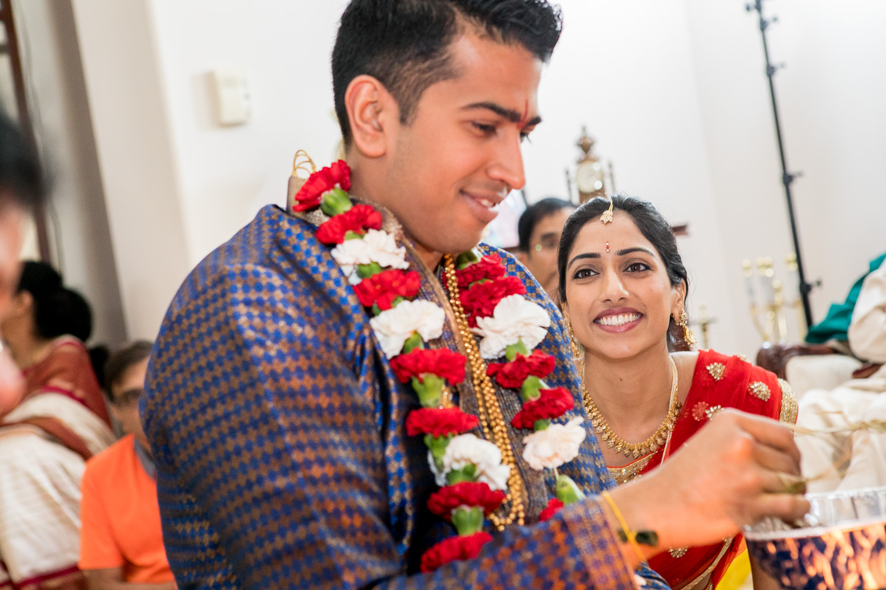 bride talks sweet nothings to indian groom while observing fire ceremony