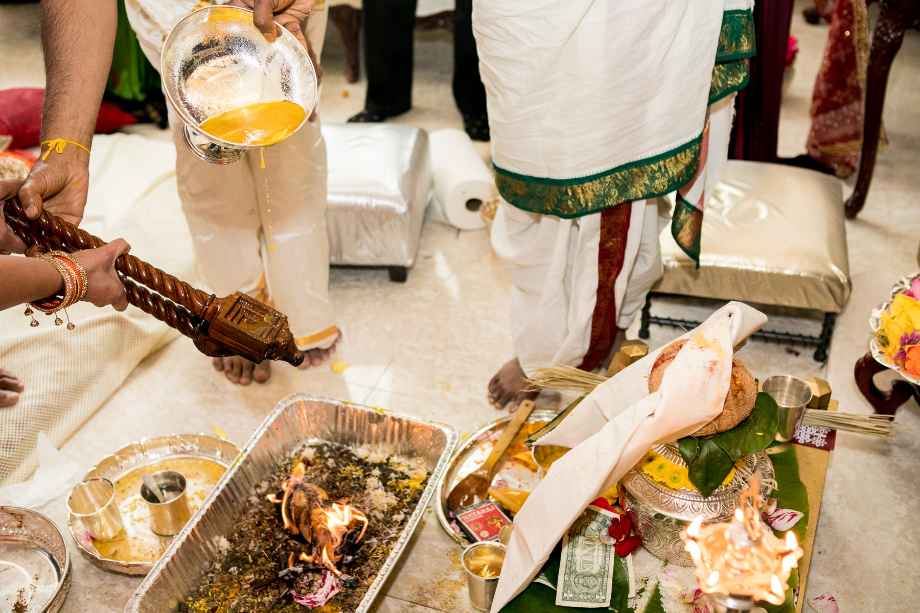ghee poured on sacred fire during indian wedding in whittier