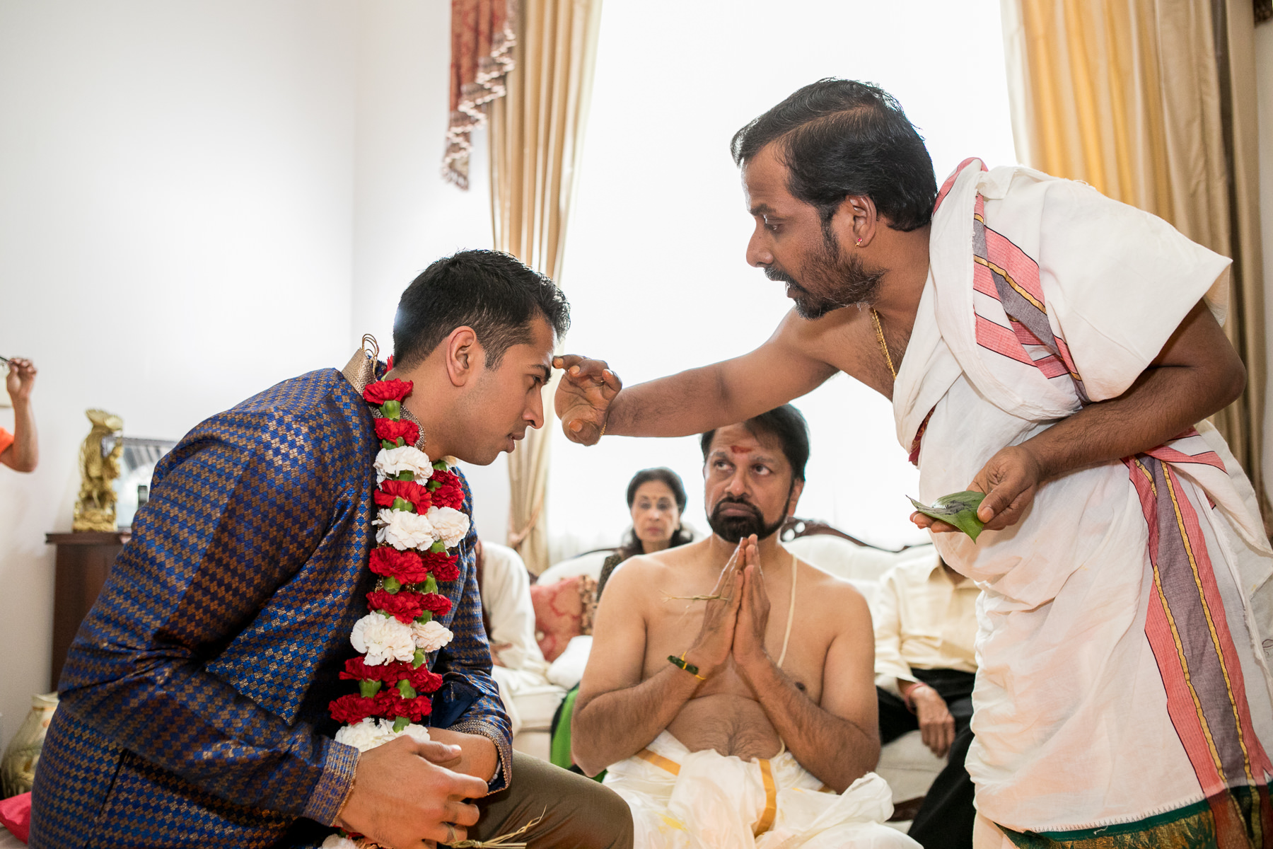 hindu priest applies sacred ash to groom's forehead during pre Indian wedding rituals
