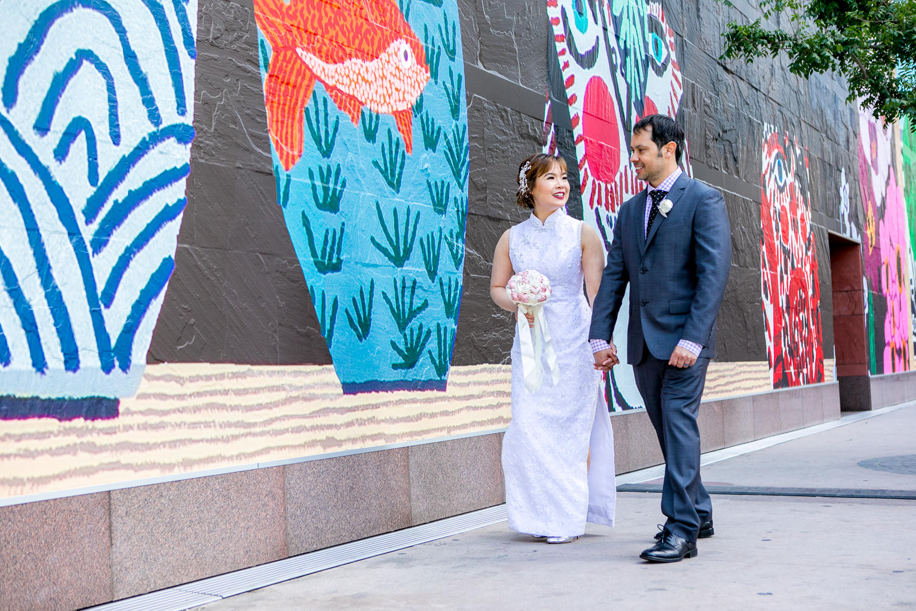 bride and groom stroll in front of mural at museum of contemporary art wedding in los angeles
