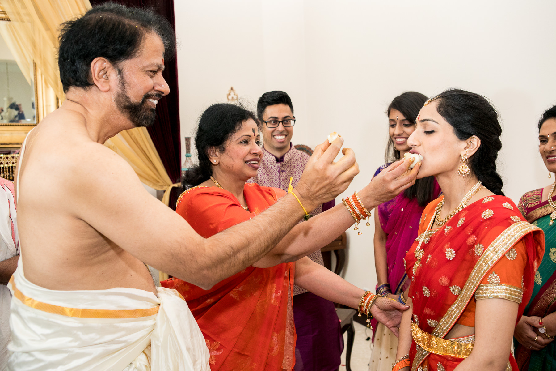 indian in laws feed bride sweets during indian wedding photographer in southern california