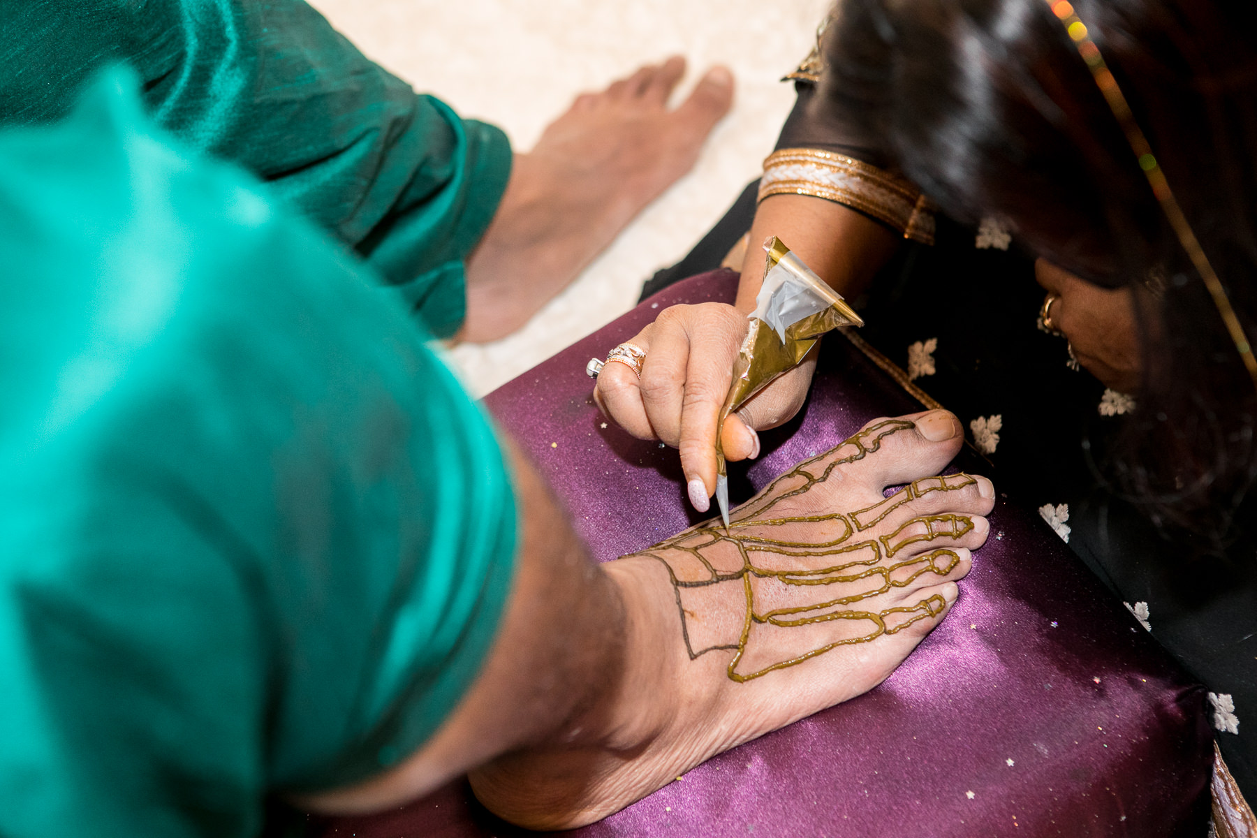 groom gets bone structure henna on foot during mendhi ceremony in whittier wedding photographer