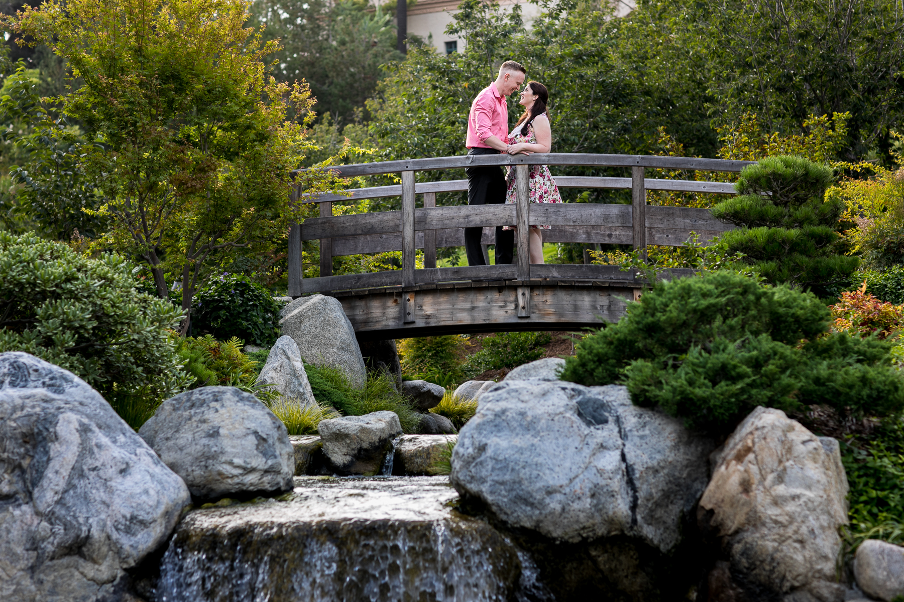wide shot of couple having a moment on bridge at japanese garden in san diego engagement session
