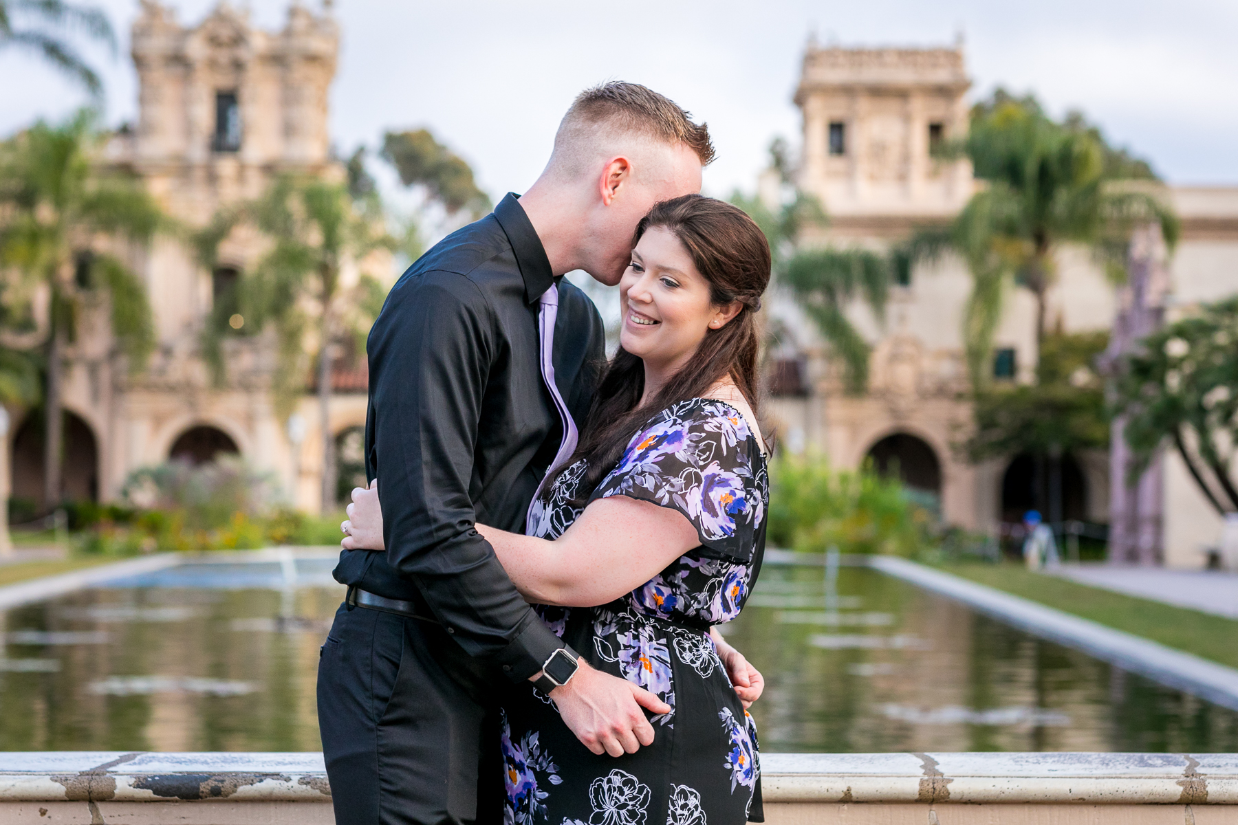guy whispers sweets nothings into girl's ear during balboa park engagement session