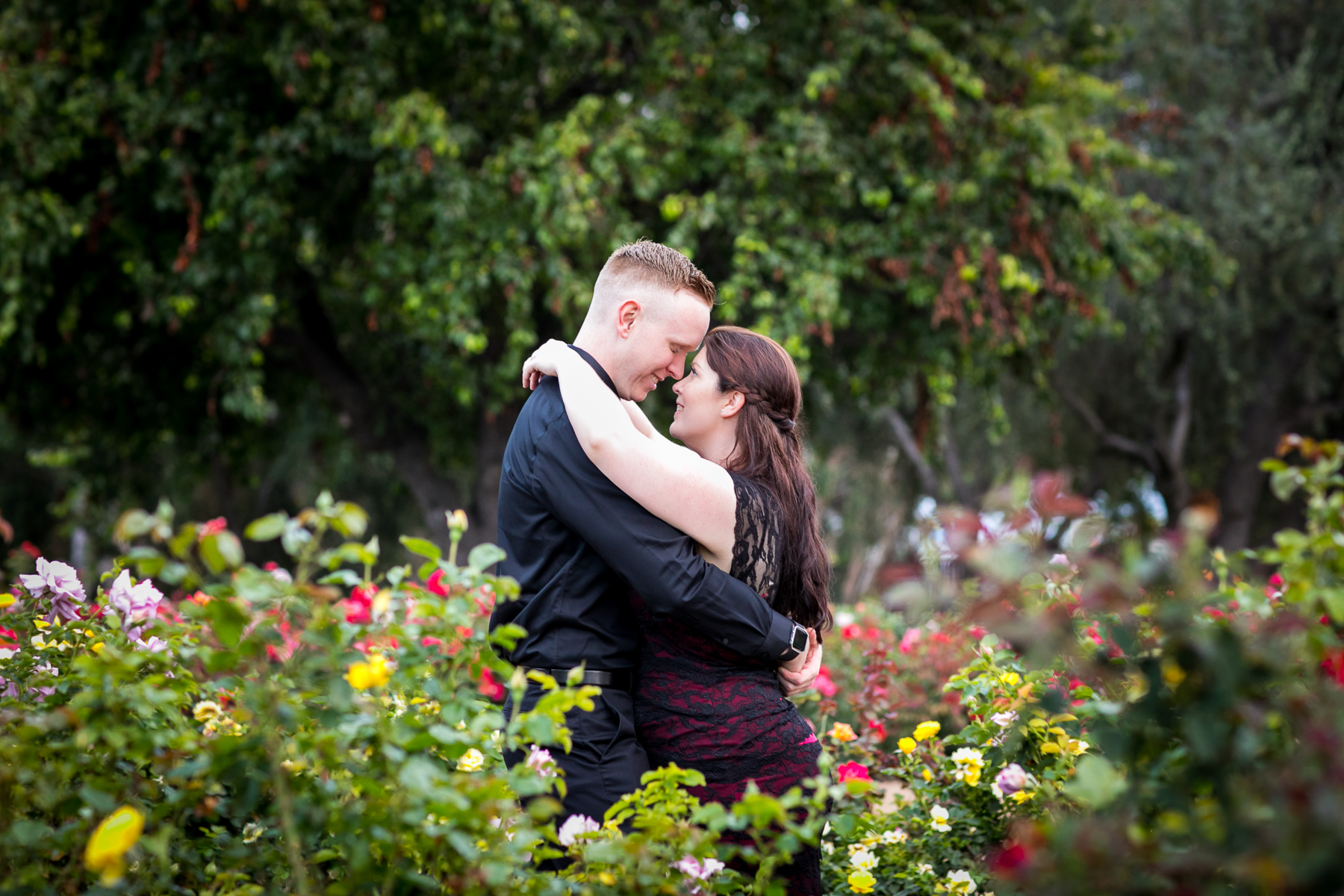 couple stare into each other's eyes at rose garden in balboa park engagement session