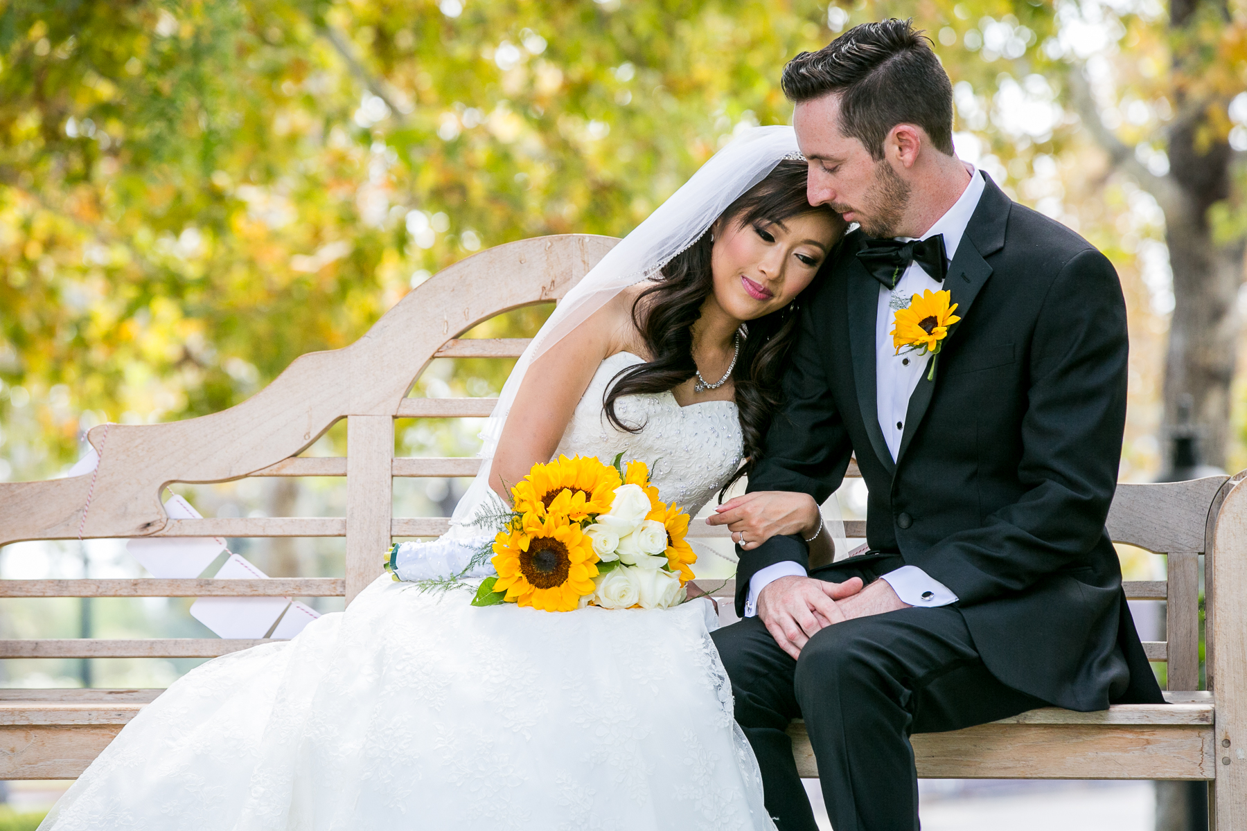 portrait of bride and groom sitting on bench at sunflower themed summit house wedding