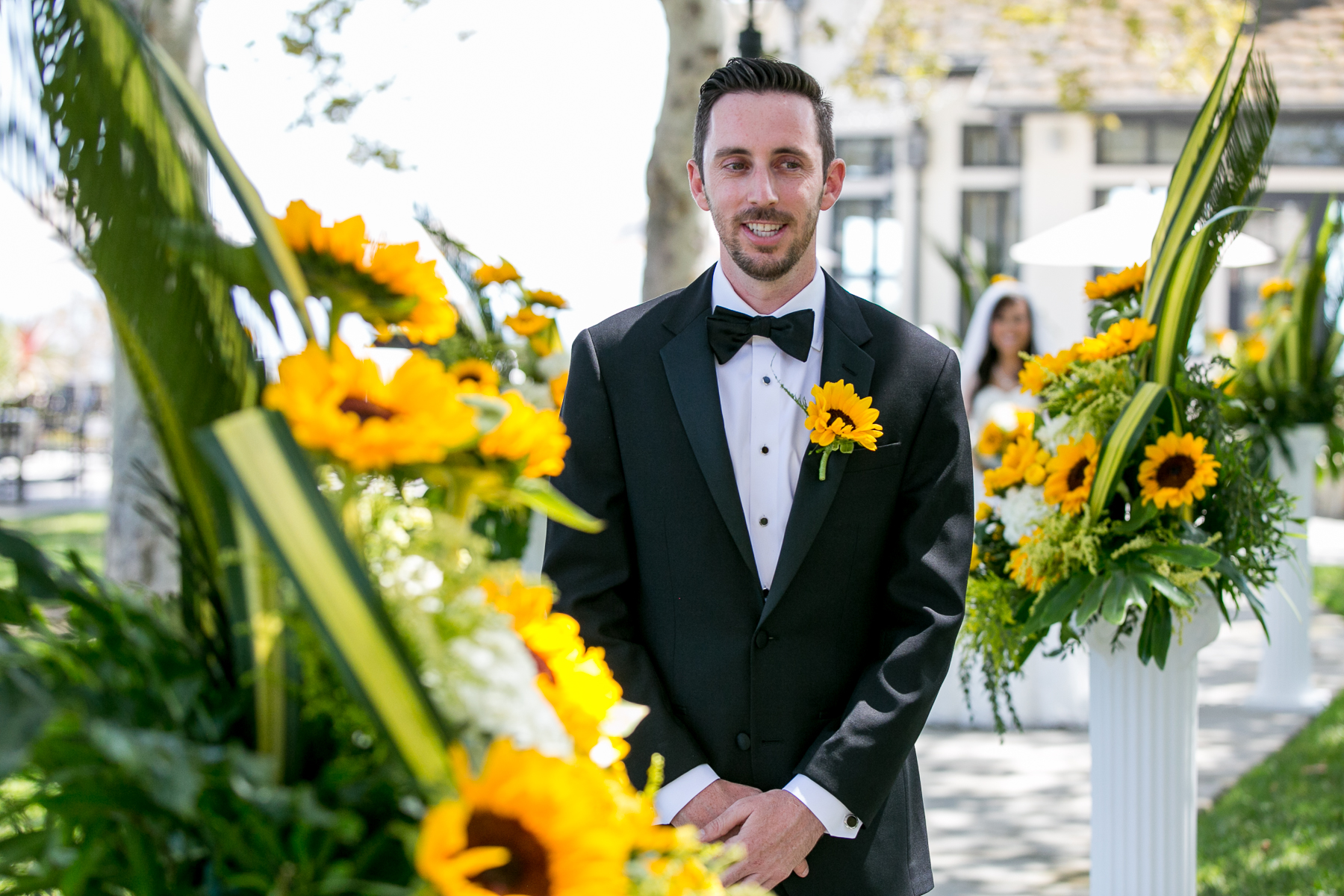 groom patiently waits during first look at fullerton wedding photos