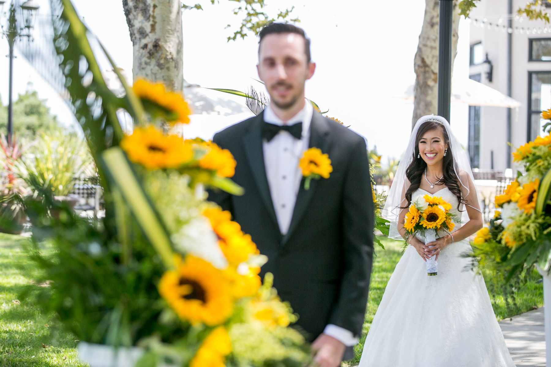 bride smiles during first look for sunflower themed wedding at summit house photos