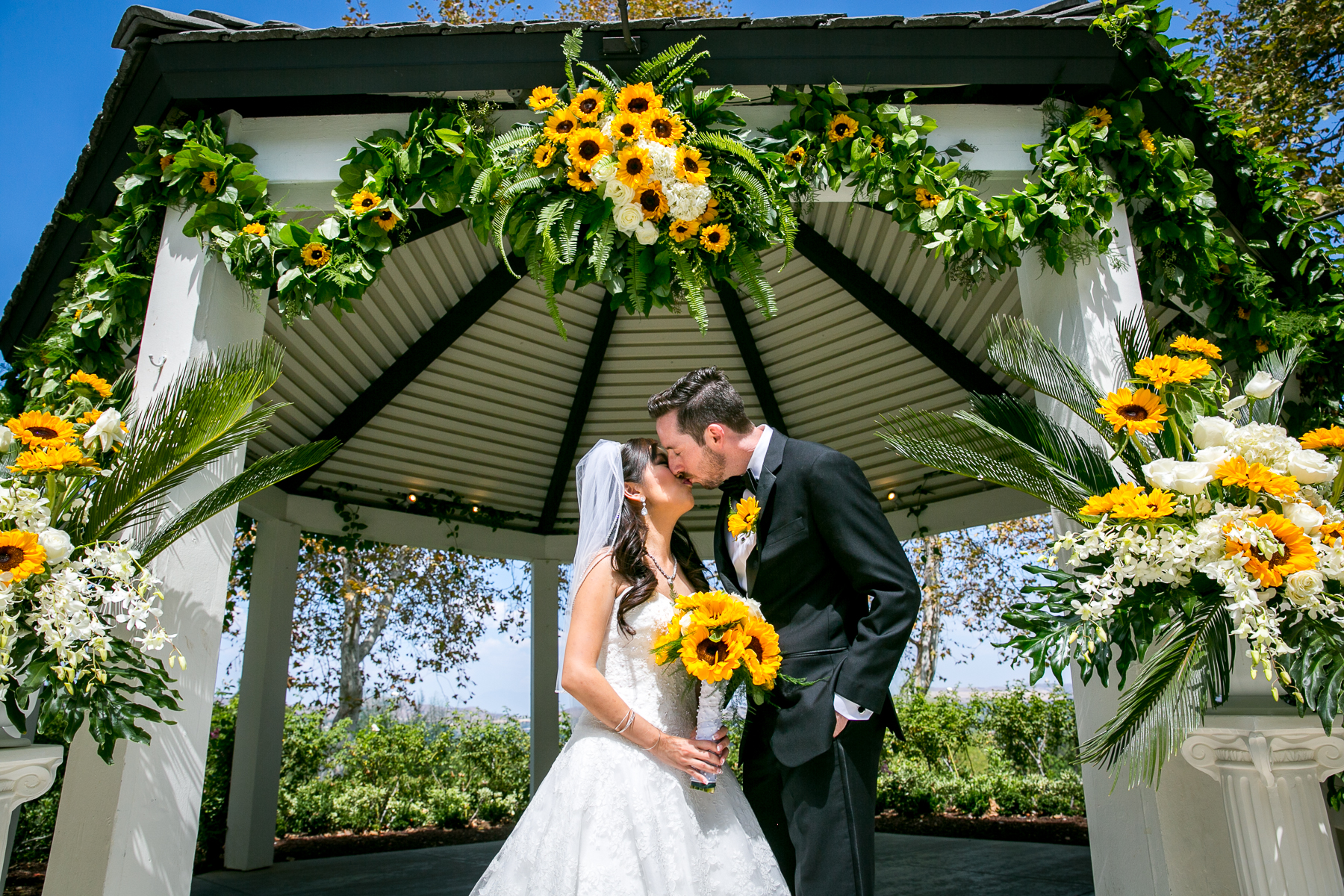 bride and groom kiss in front of gazebo at summit house wedding photos