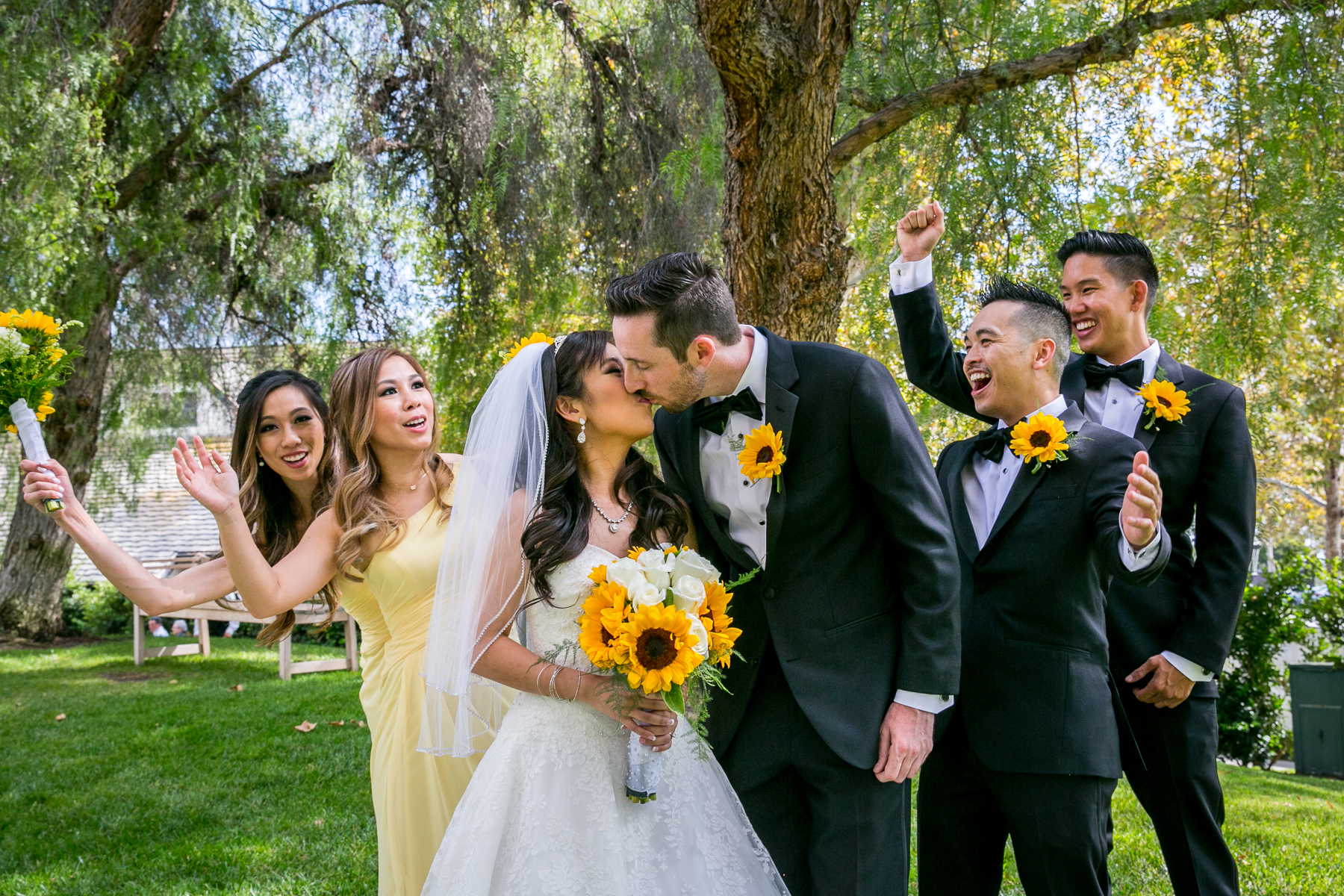 bridal party cheers as bride and groom kiss for wedding at summit house photos