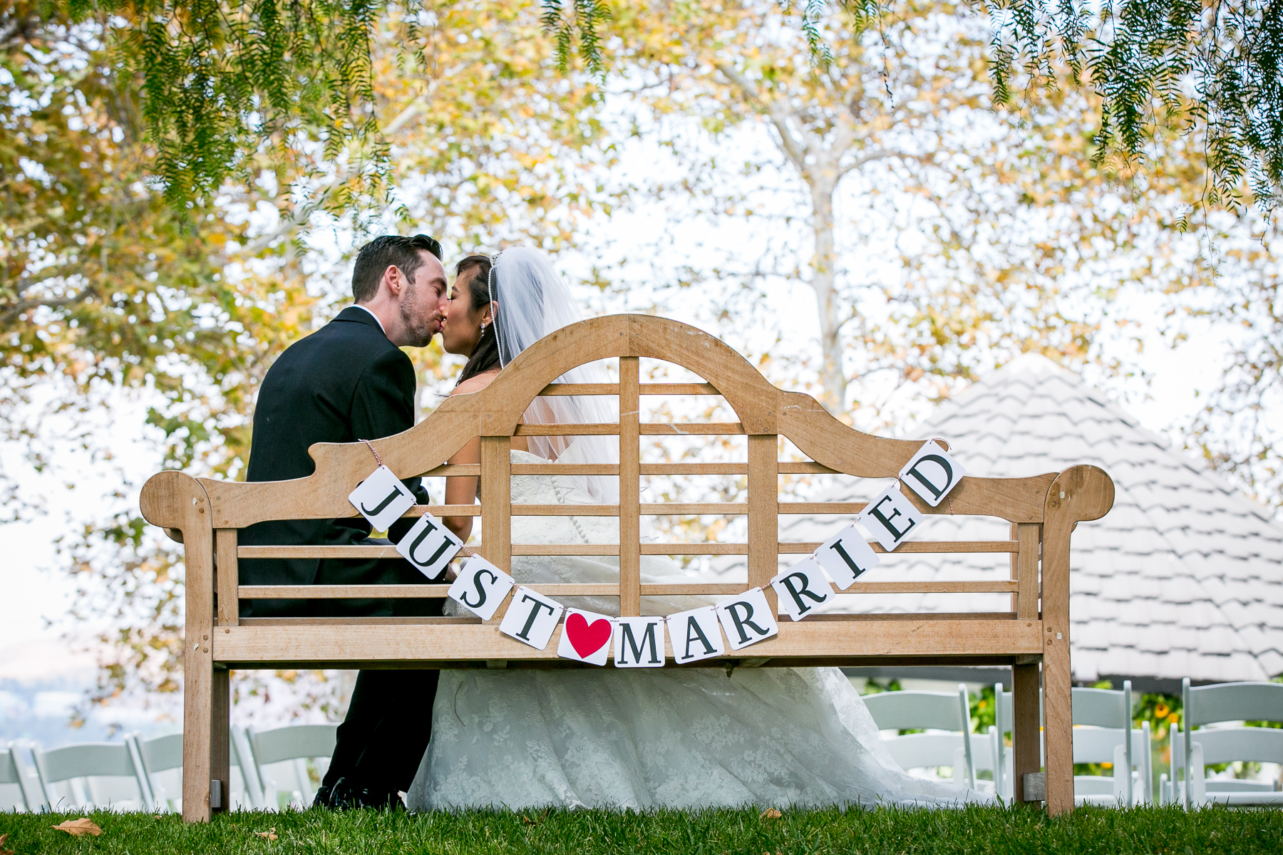 newlywed couple kiss on bench at summit house wedding photographer
