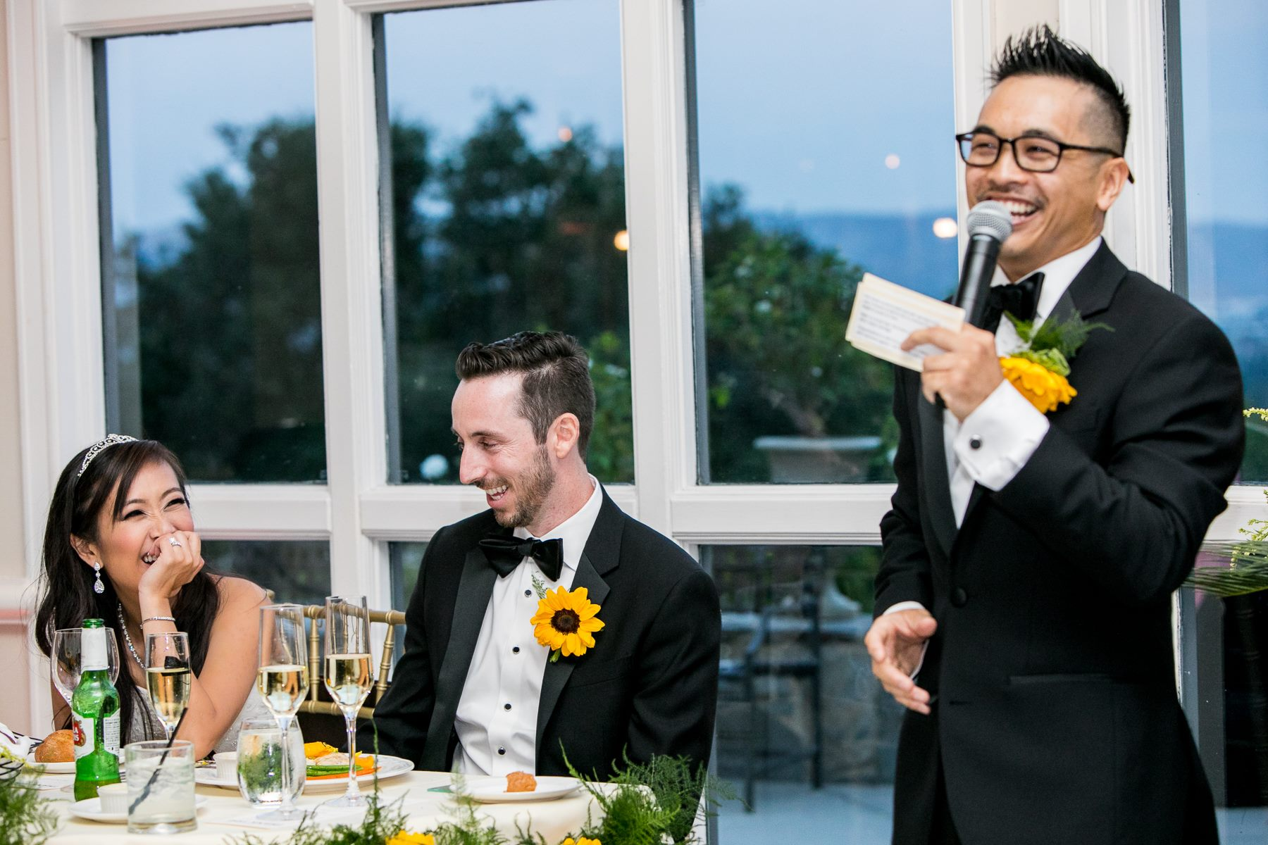 bride and groom laugh during groomsman speech at summit house wedding photography