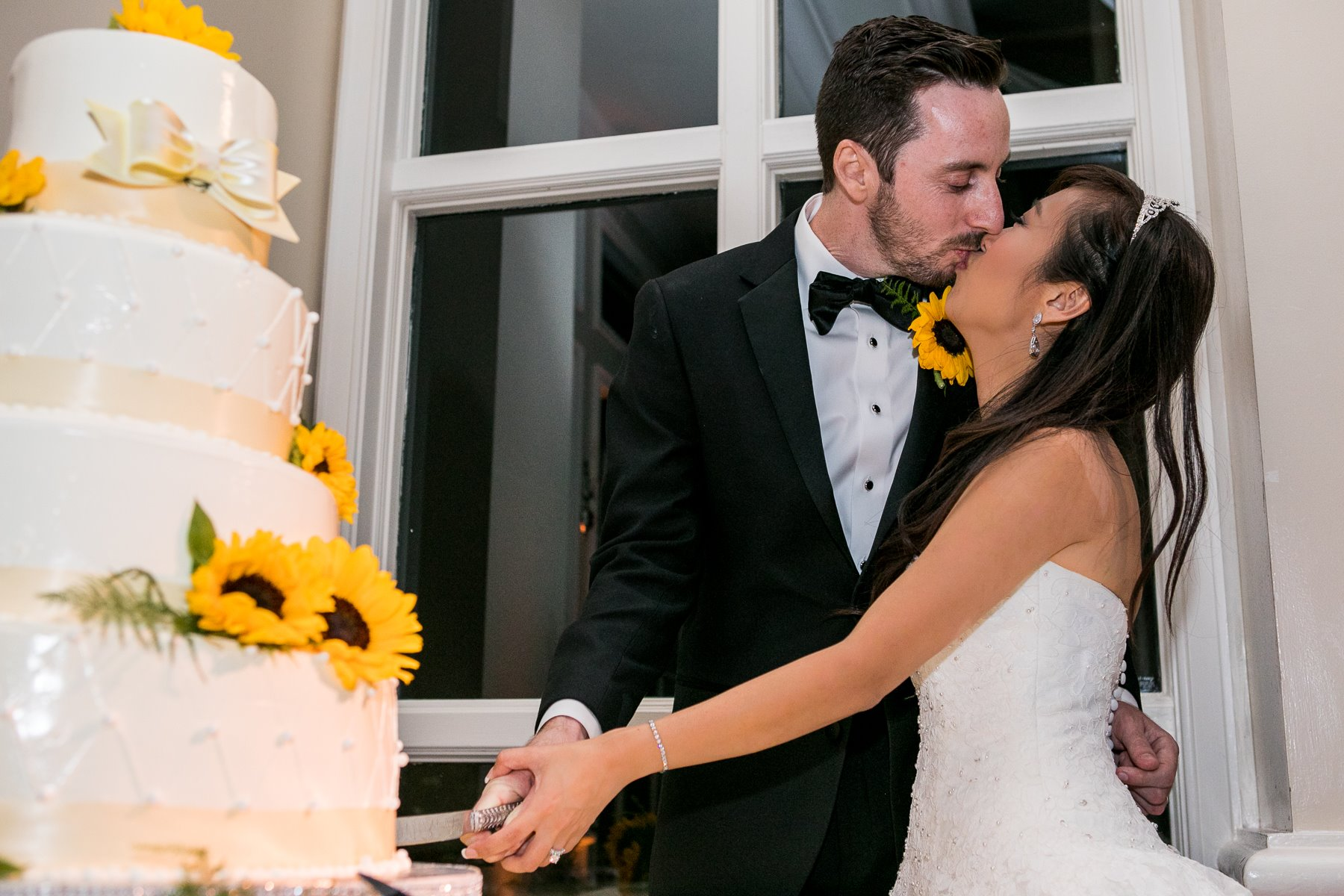 bride and groom kiss during cake cutting at fullerton wedding photos