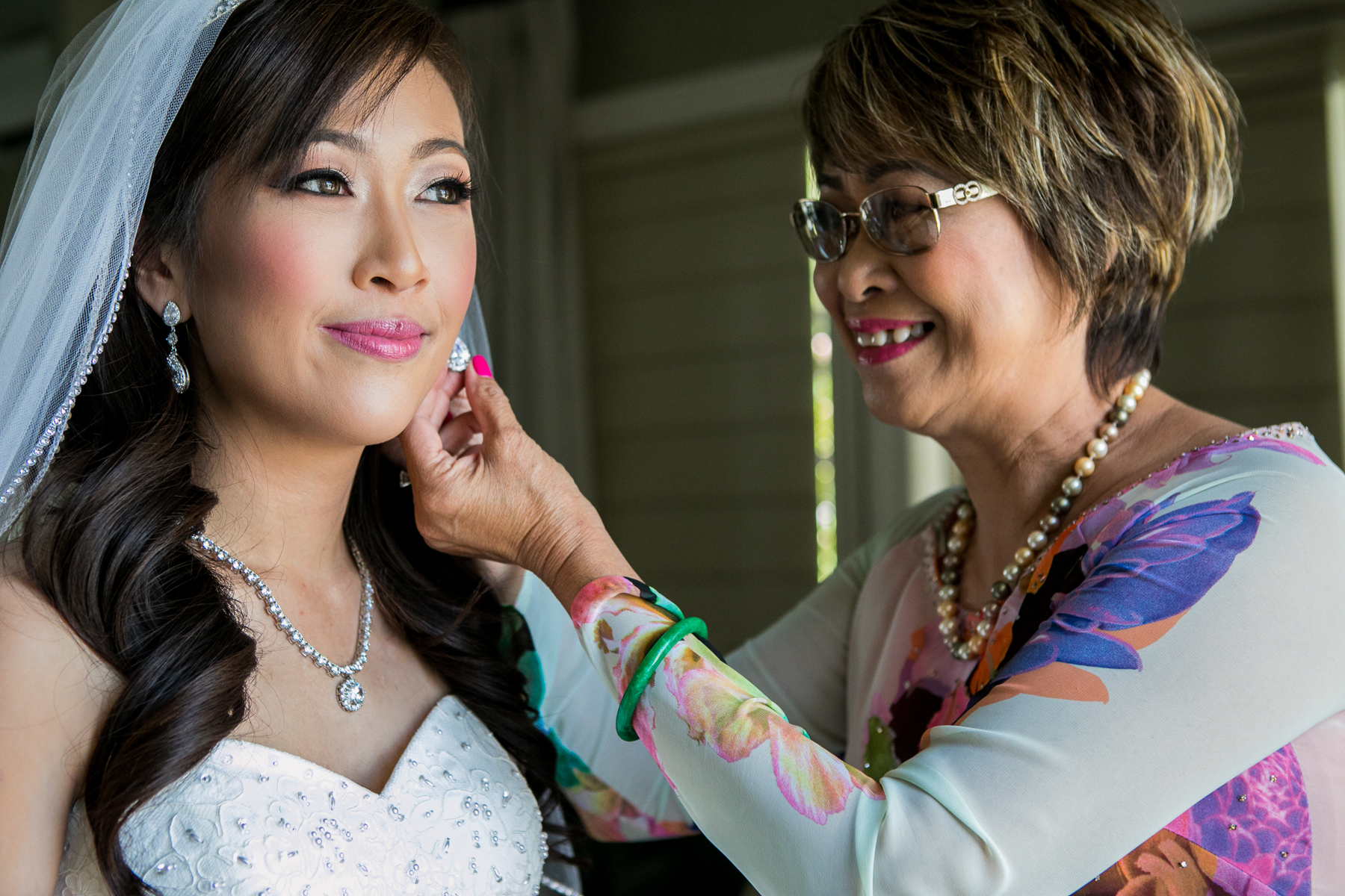 mother of bride puts jewelry on bride during fullerton wedding photo
