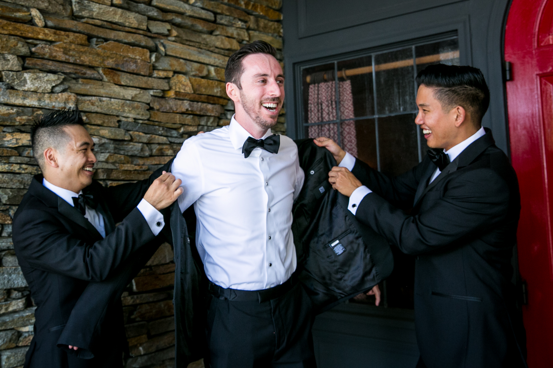 groomsmen help groom with jacket while getting ready at summit house wedding
