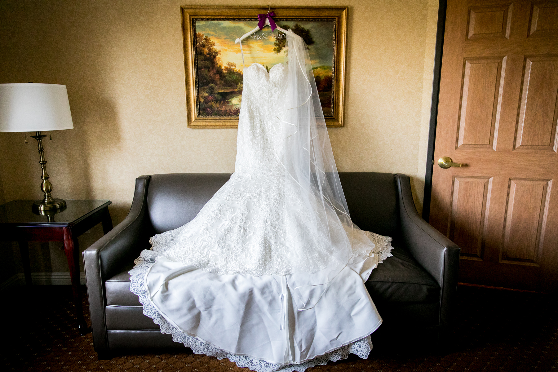 stunning wedding dress draped on painting over couch at ayres hotel in corona wedding