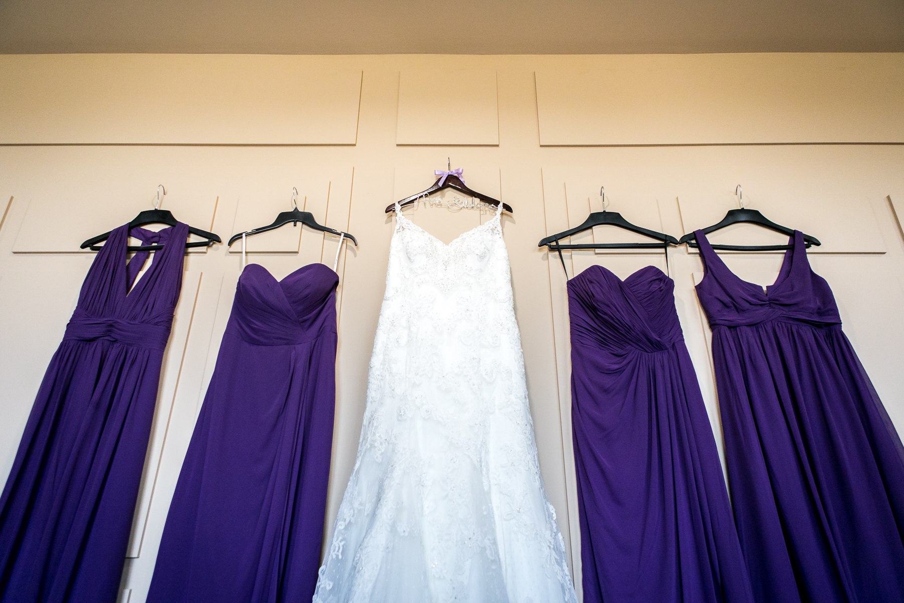 wedding dress with bridesmaids dresses hanged during getting ready at wedding at rancho santa margarita