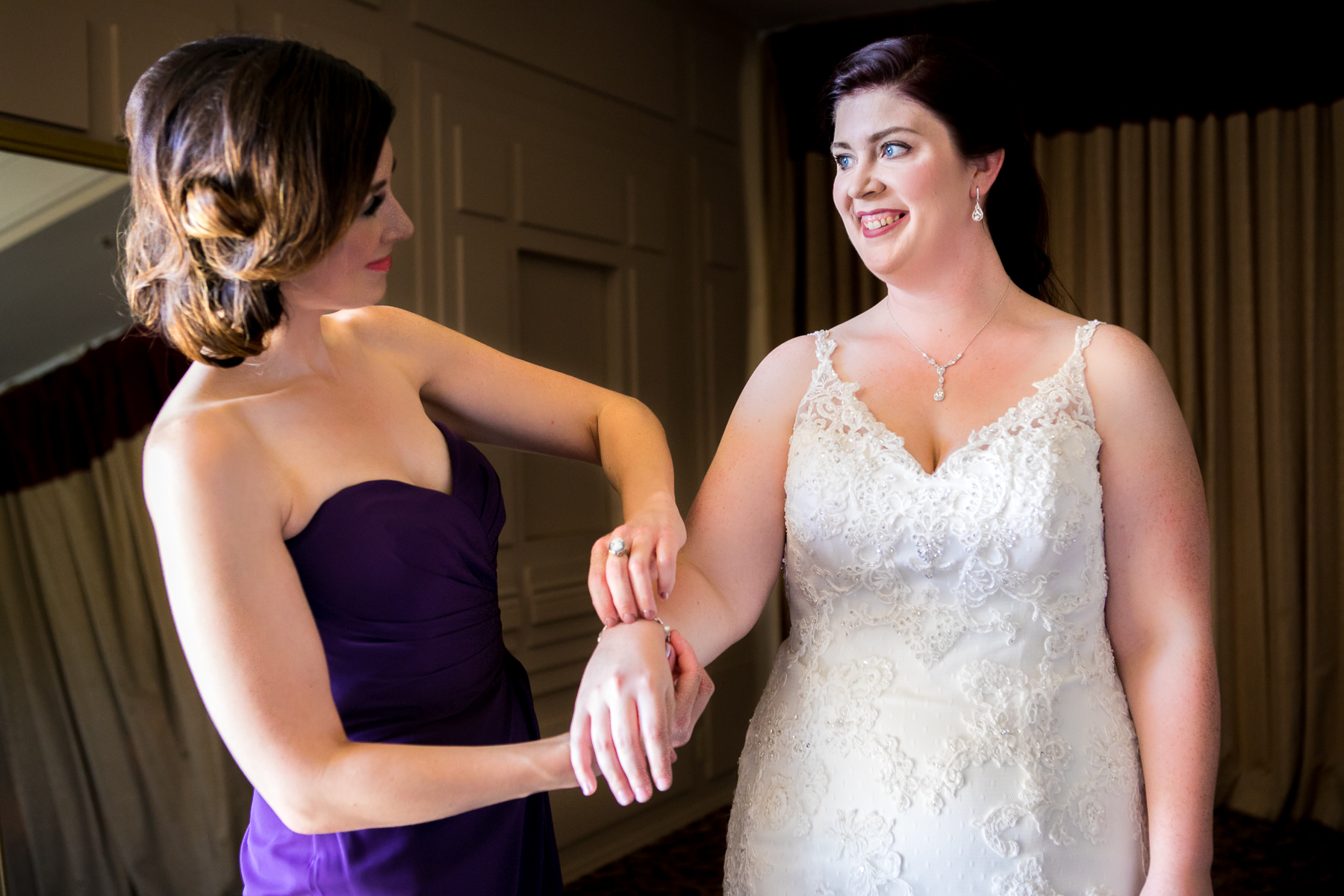 maid of honor puts jewelry on bride dove canyon wedding photographer