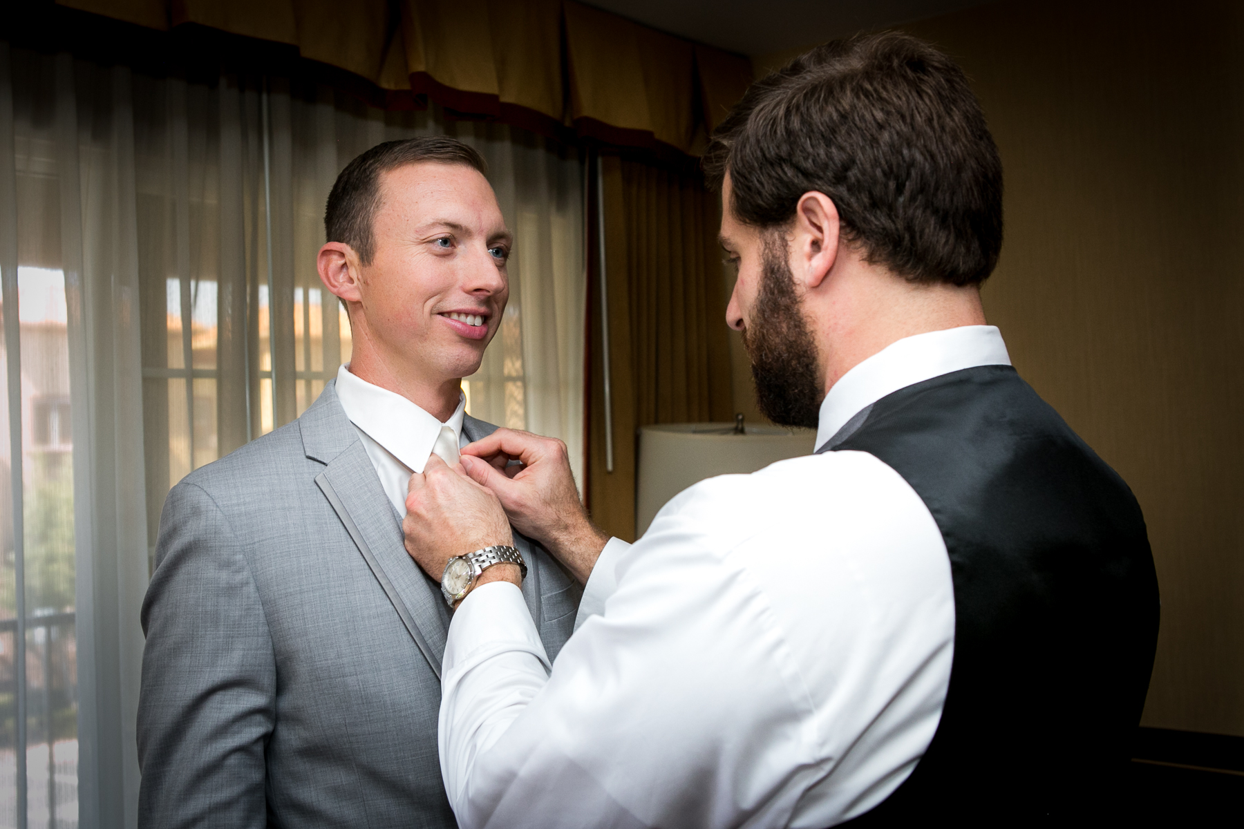 best man adjust groom's tie during getting ready at wedding at ayres hotel in corona