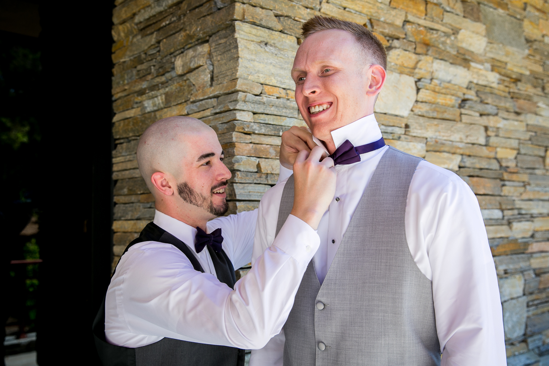 best man puts on groom's bowtie at dove canyon wedding photographer