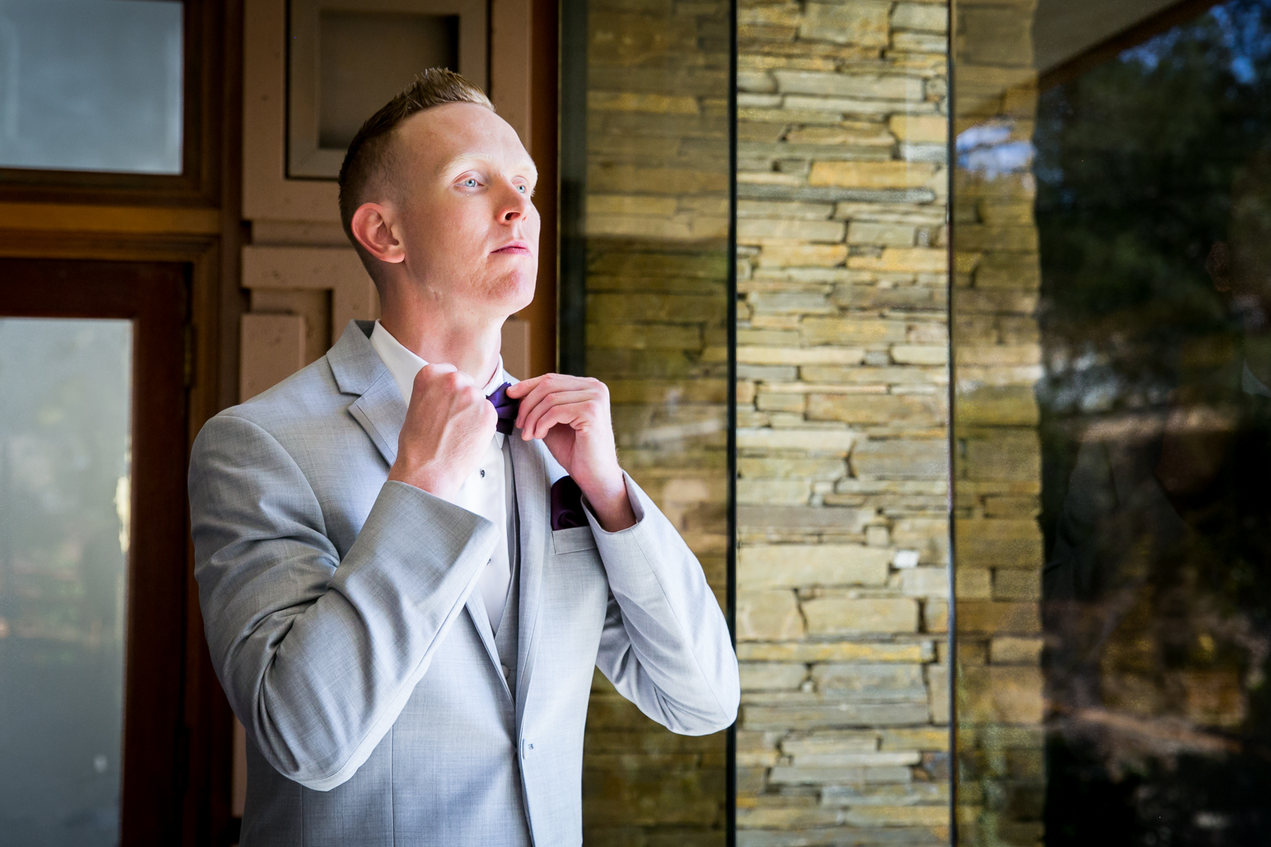 dapper groom purple bowtie adjusting at wedding at dove canyone photographer