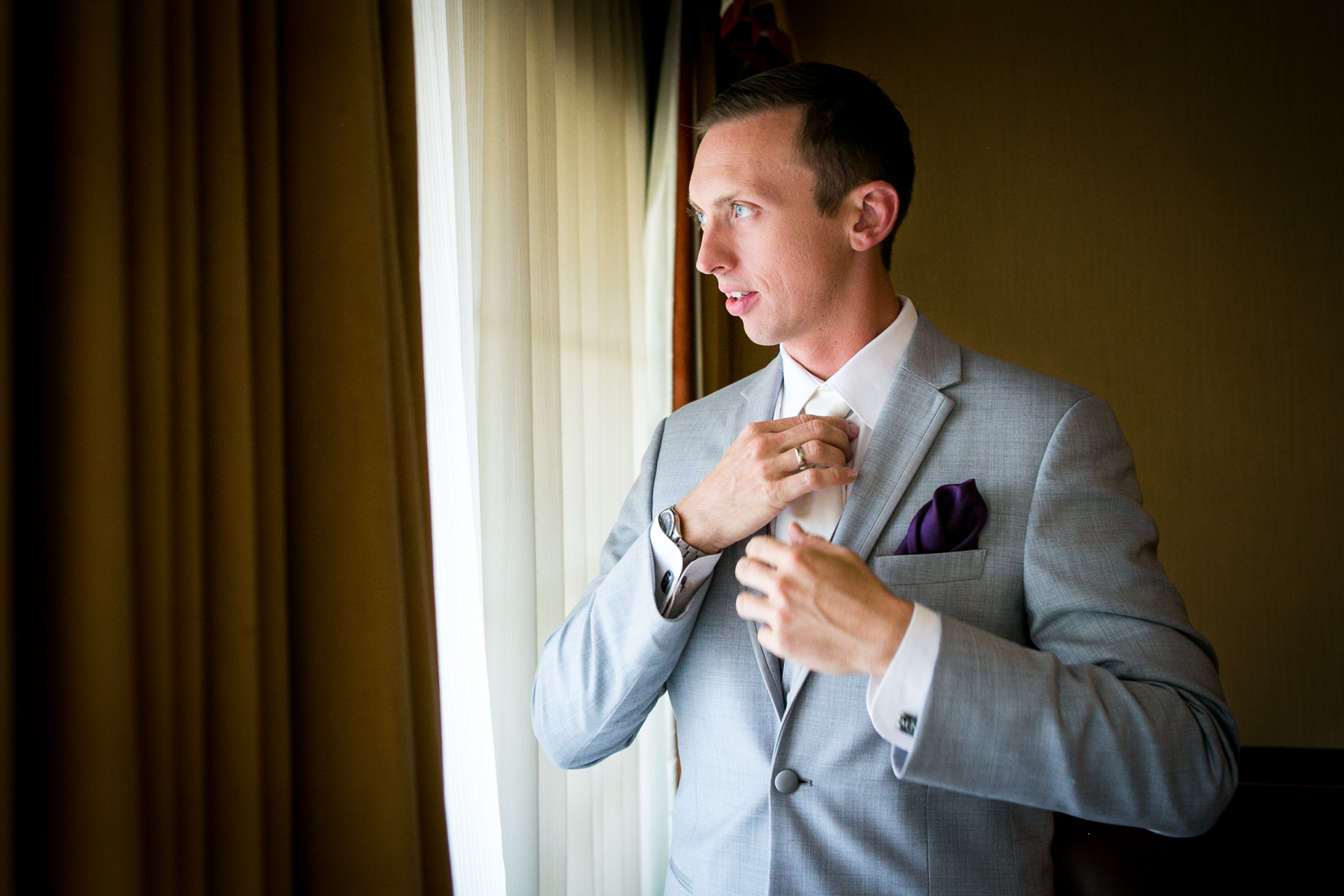 groom adjusts tie while looking out window at corona wedding photographer