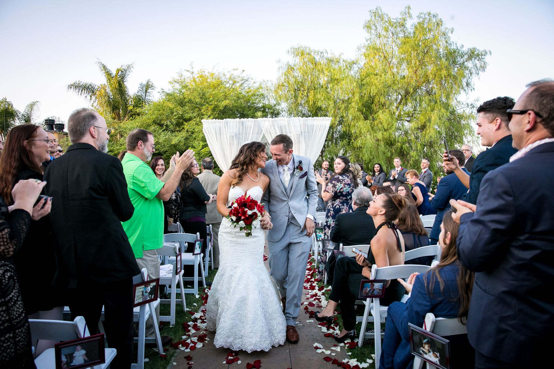 newly married couple walk down the aisle together at wedding in corona photographer