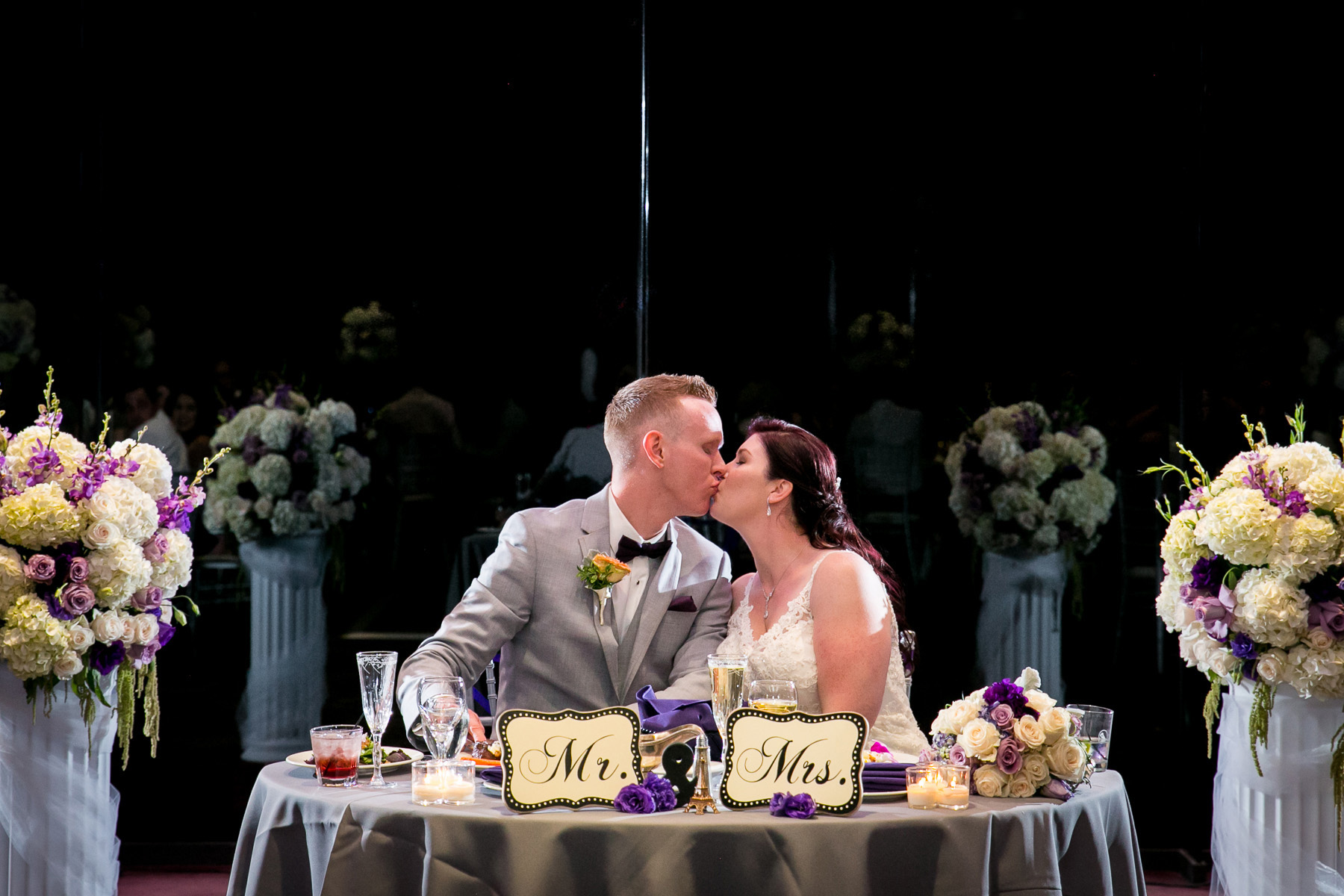 bride and groom kiss at table during wedding reception at dove canyon photographer