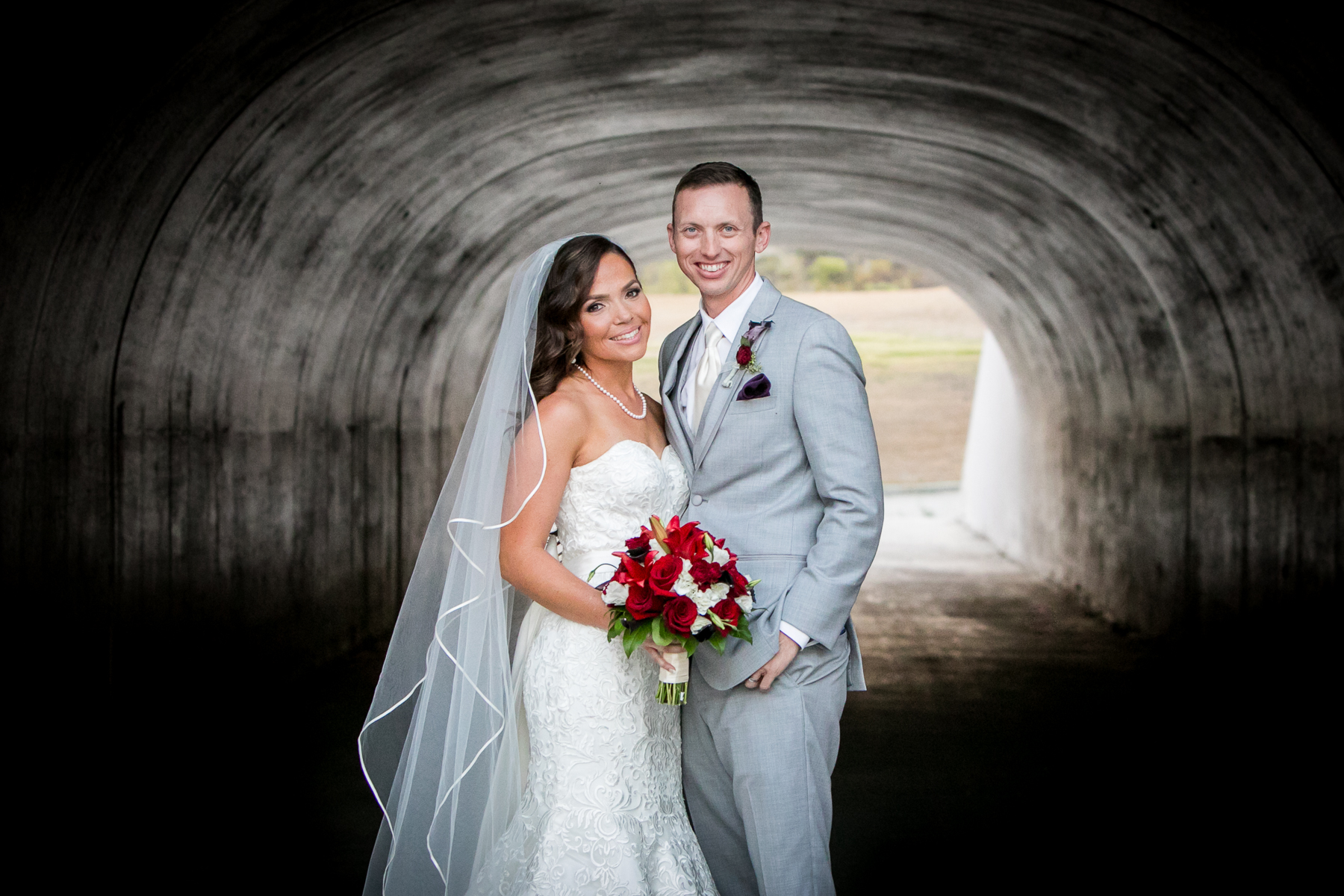 portrait under tunnel of bride and groom at wedding at the retreat photos
