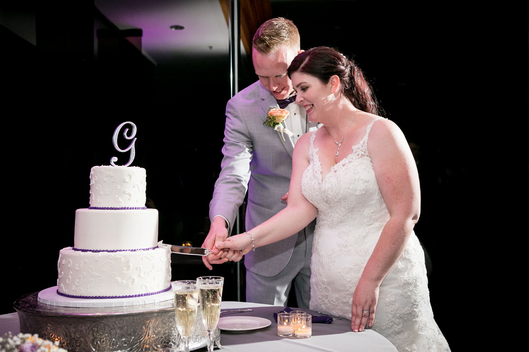 bride and groom cut into wedding cake at orange county wedding photos