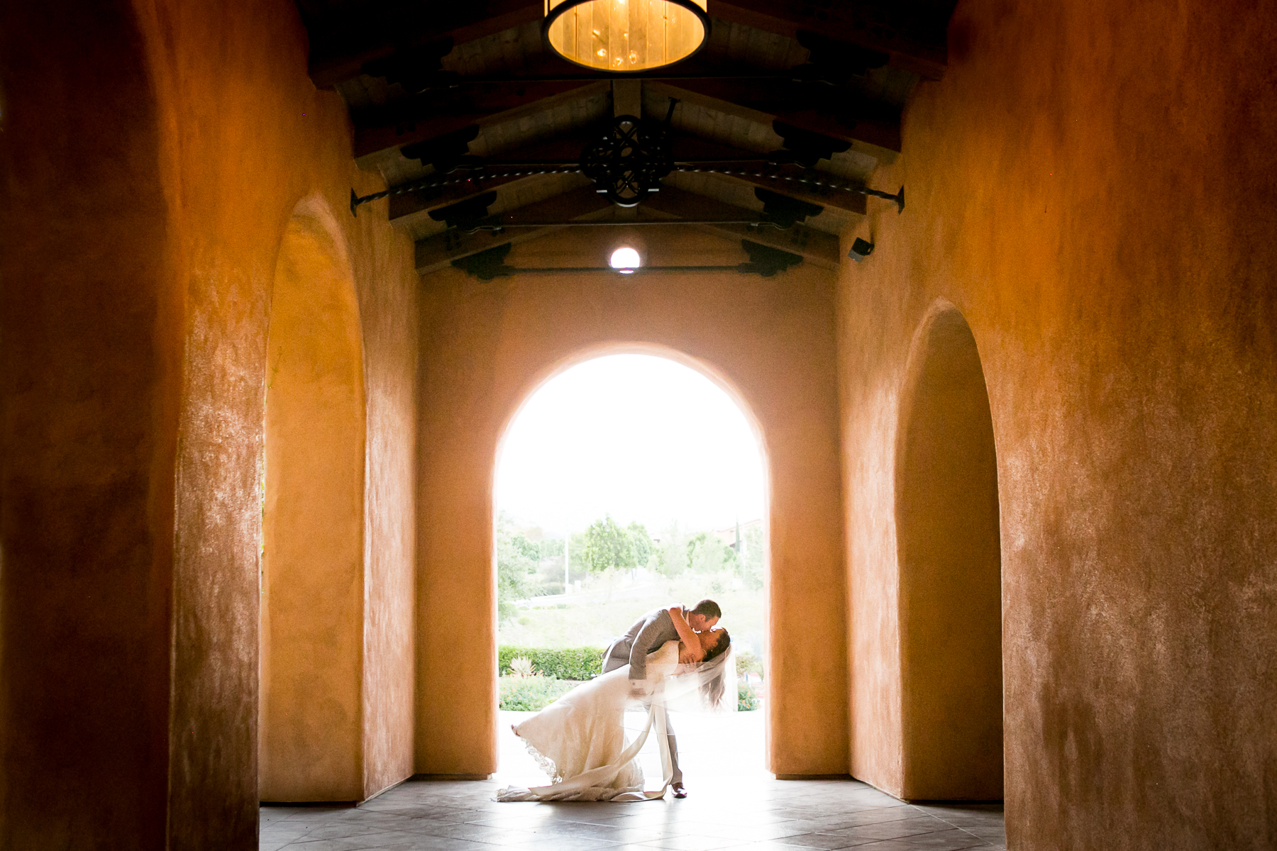 groom dips bride and kiss at wedding venue photographer in corona