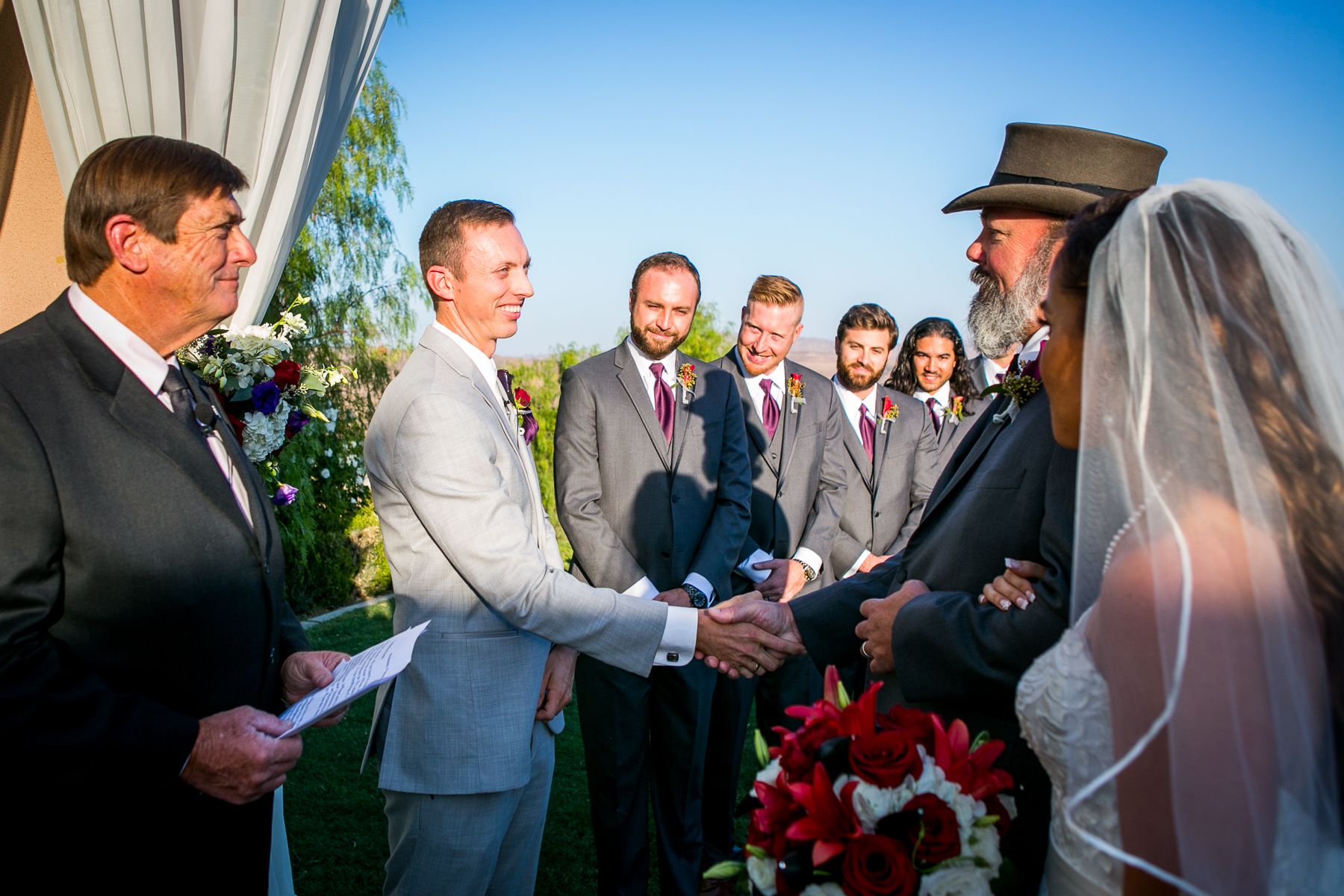 father of bride shakes groom's hand during ceremony wedding at the champion's club at the retreat