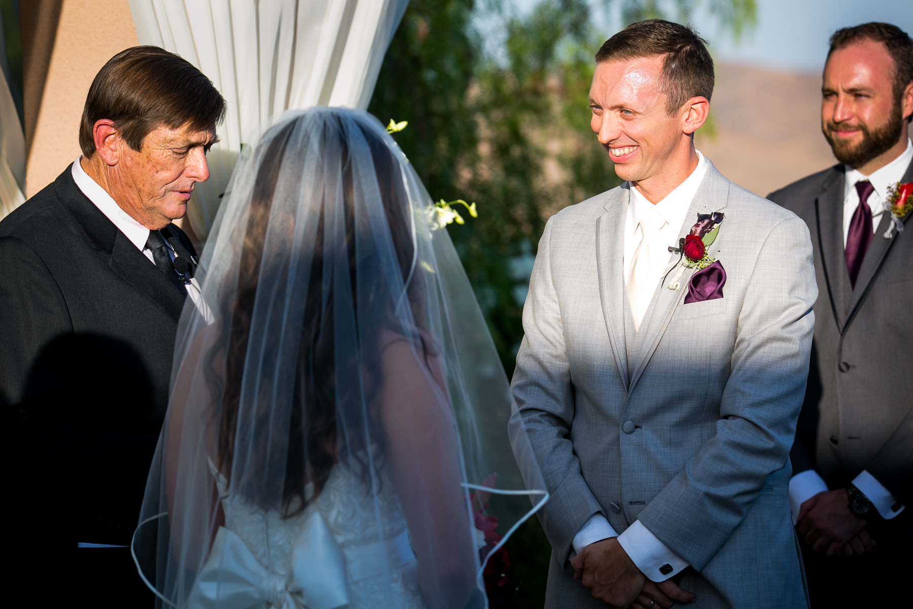 groom can't stop smiling at bride during ceremony at corona wedding photos