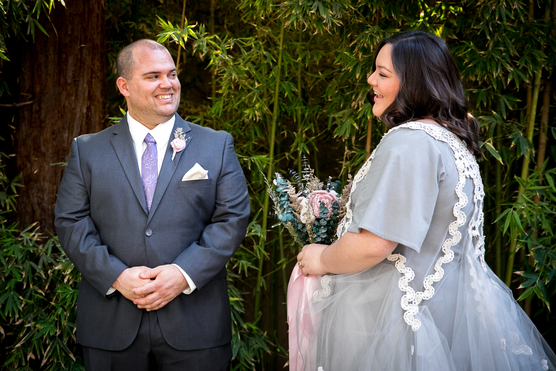 groom all smiles after seeing bride for first time in her wedding dress during first look at storrier stearns wedding photographer
