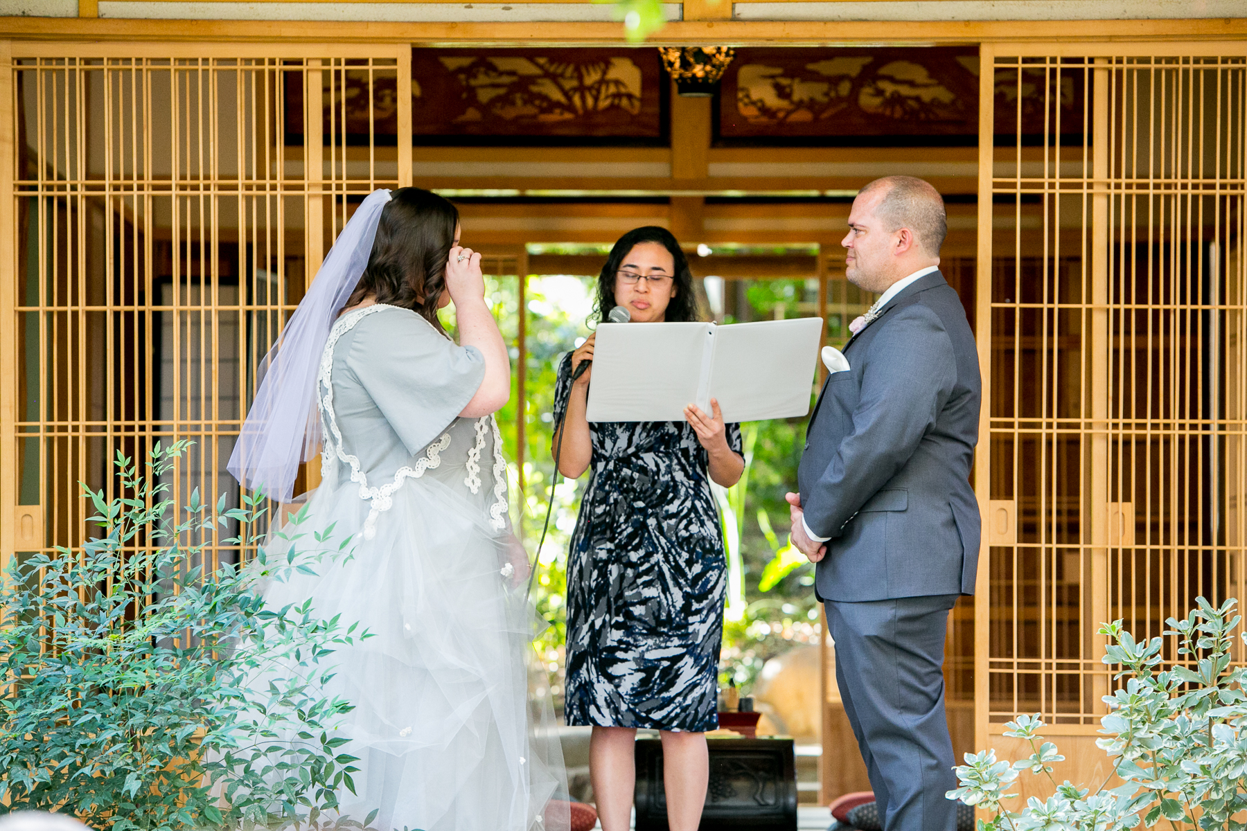 bride wipes tear from eyes during wedding ceremony at storrier stearns photos