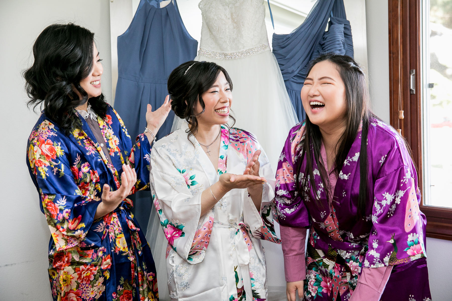 bride and bridesmaids laugh while getting ready at mccoy equestrian center wedding photos