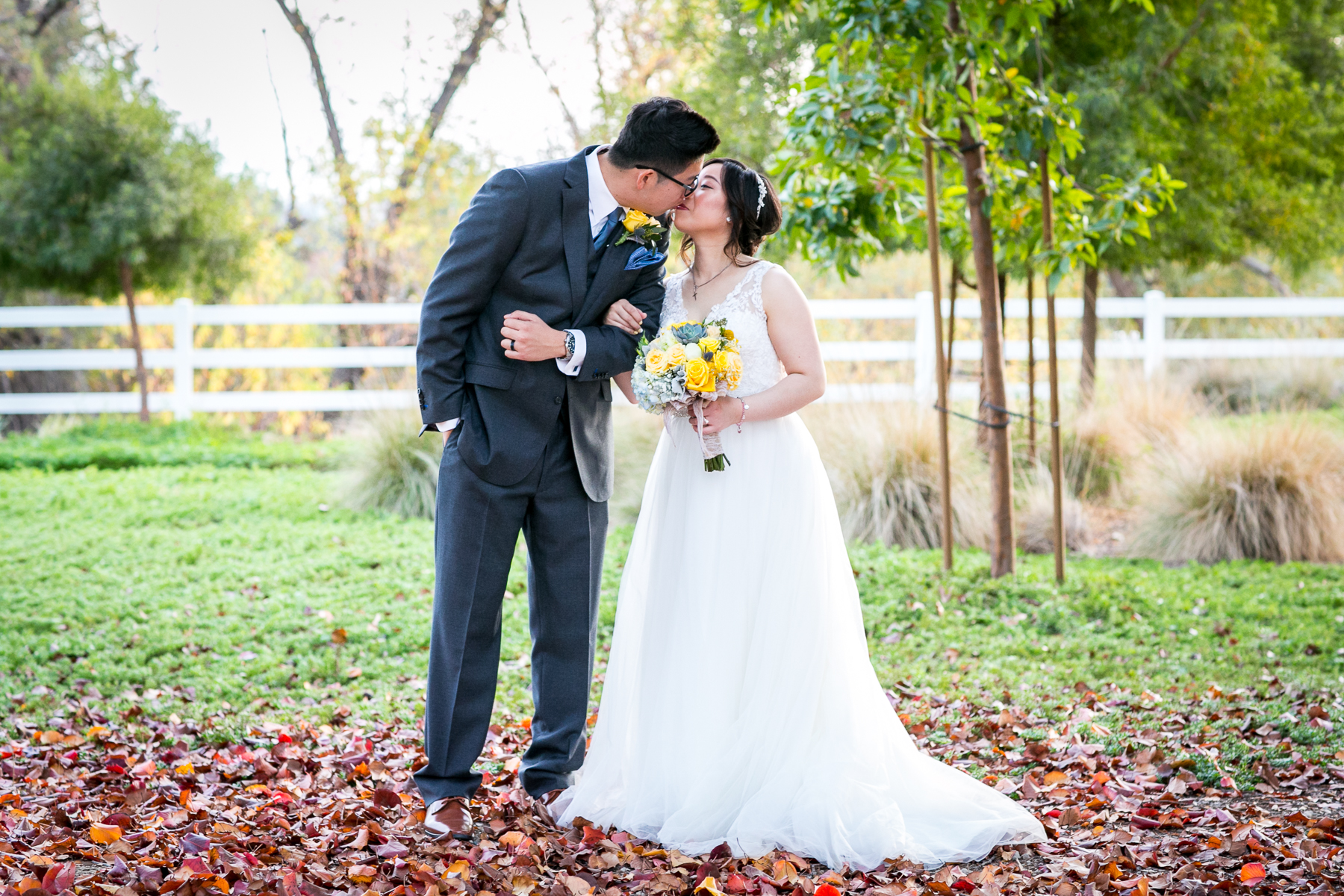 bride and groom kiss during portraits at wedding in chino photographer