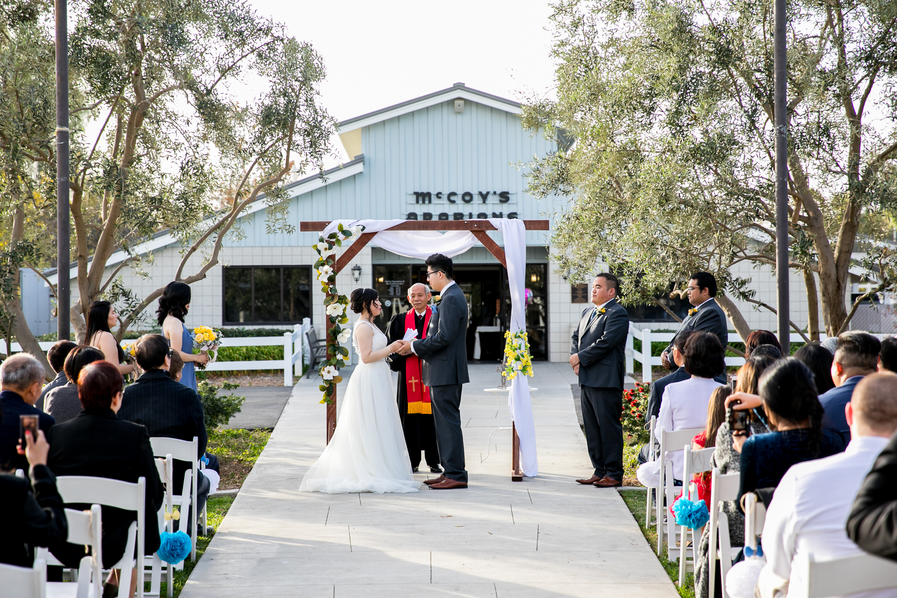 bride and groom hold hands during wedding ceremony at chino hills wedding photographer